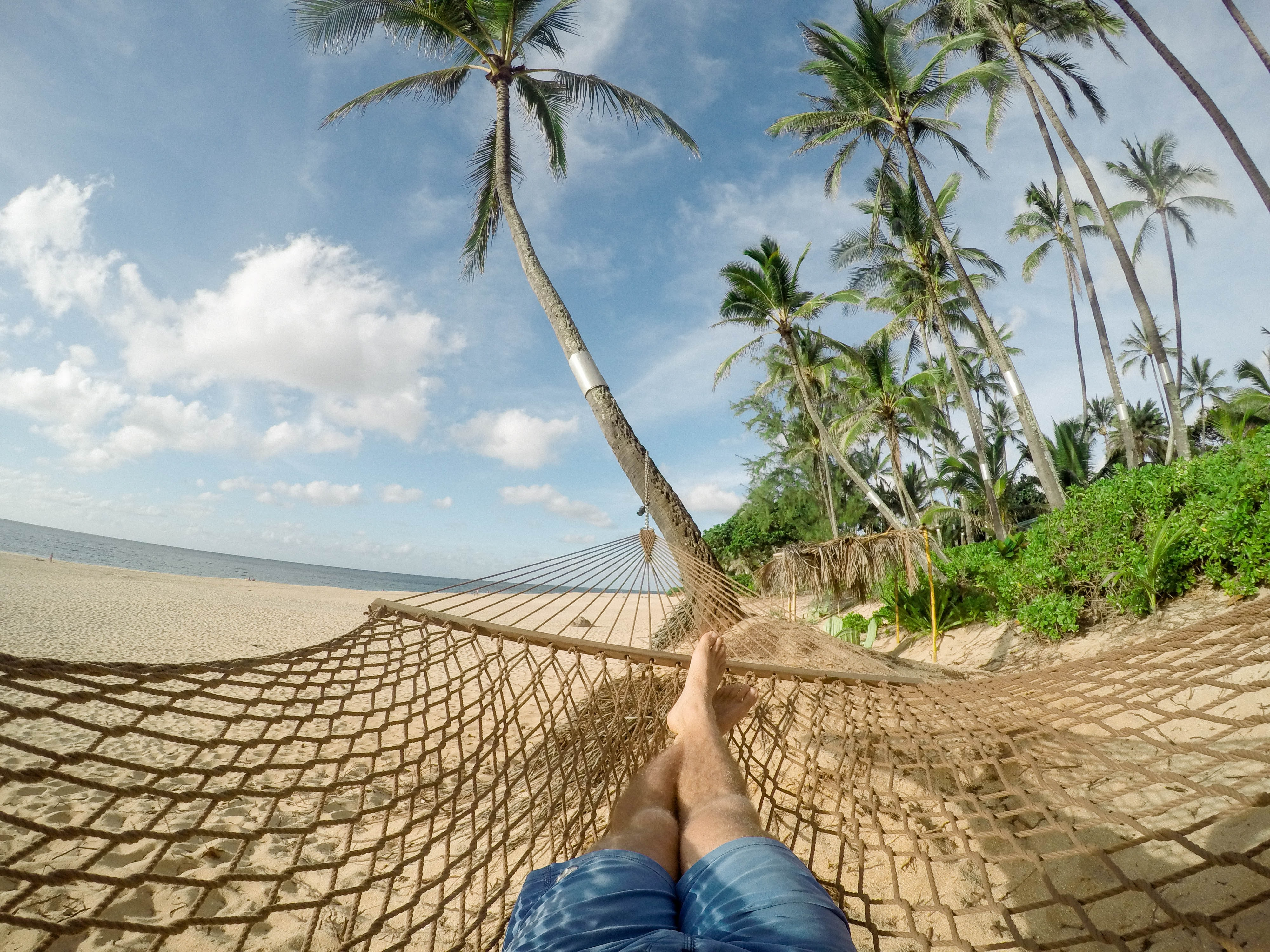 A person lying down in a hammock on the beach.
