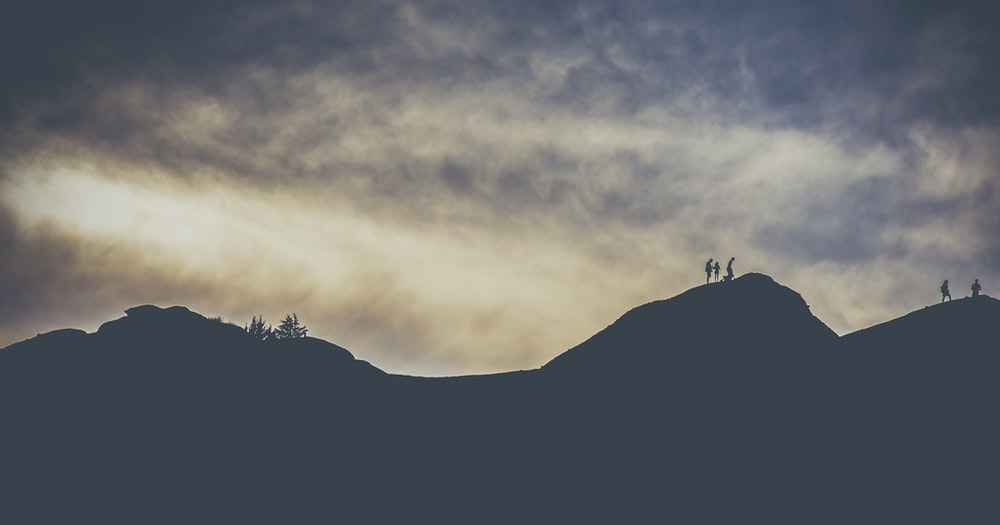 silhouette of people crossing a mountain