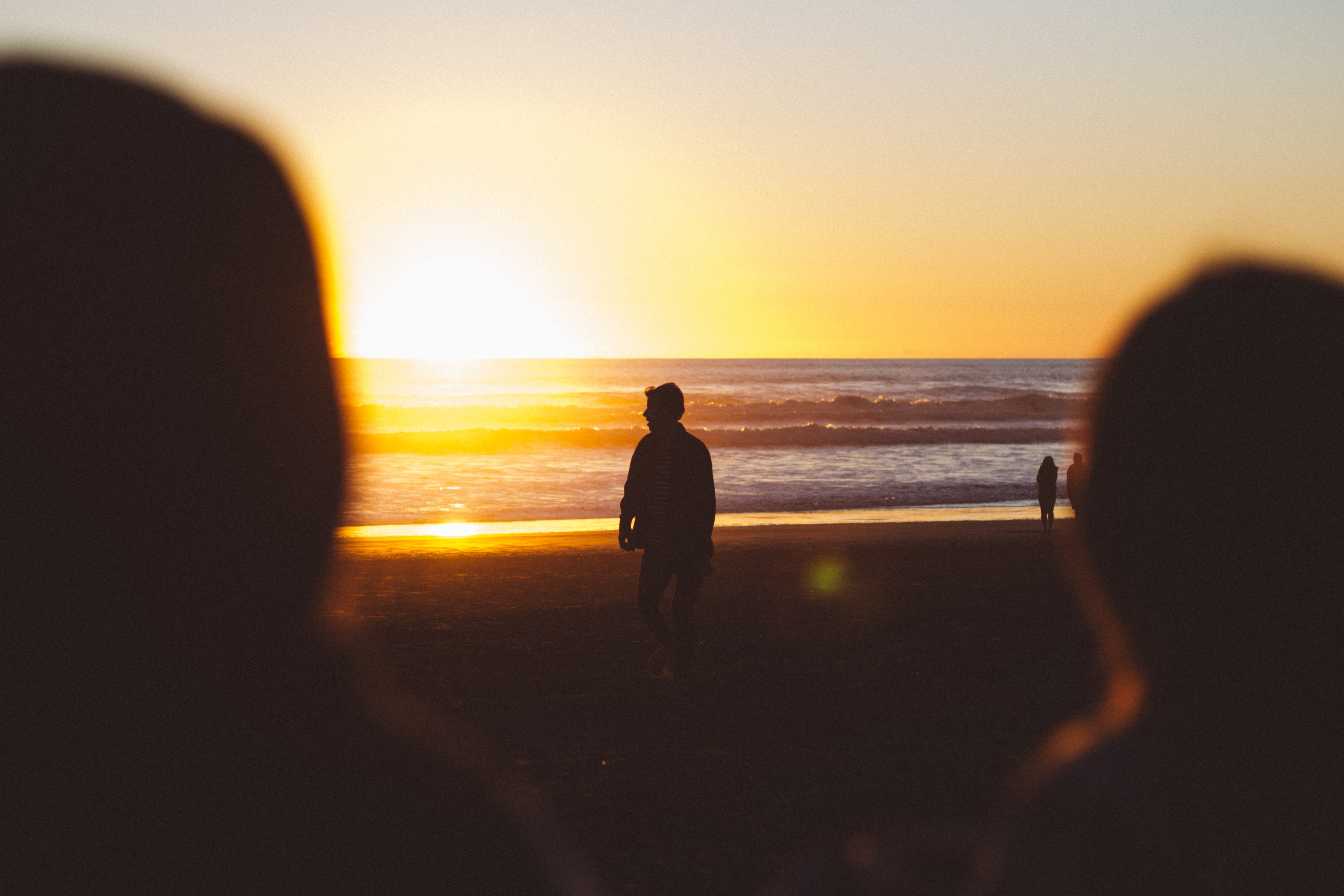Silhouette of a person on the beach, sun setting on the horizon, seen over shoulders of two blurred people in the foreground