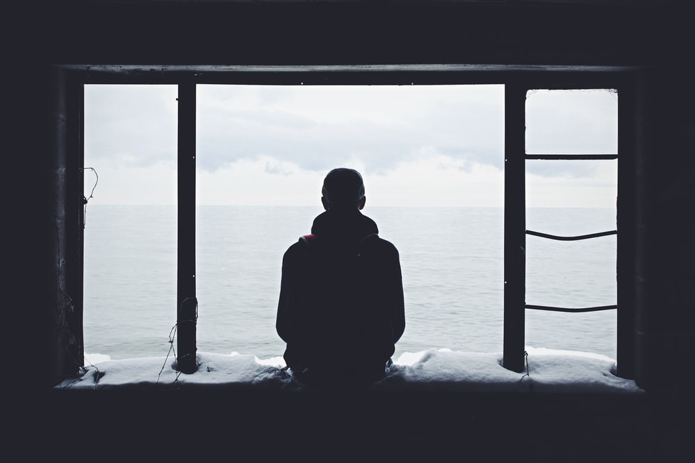 person looking out through window