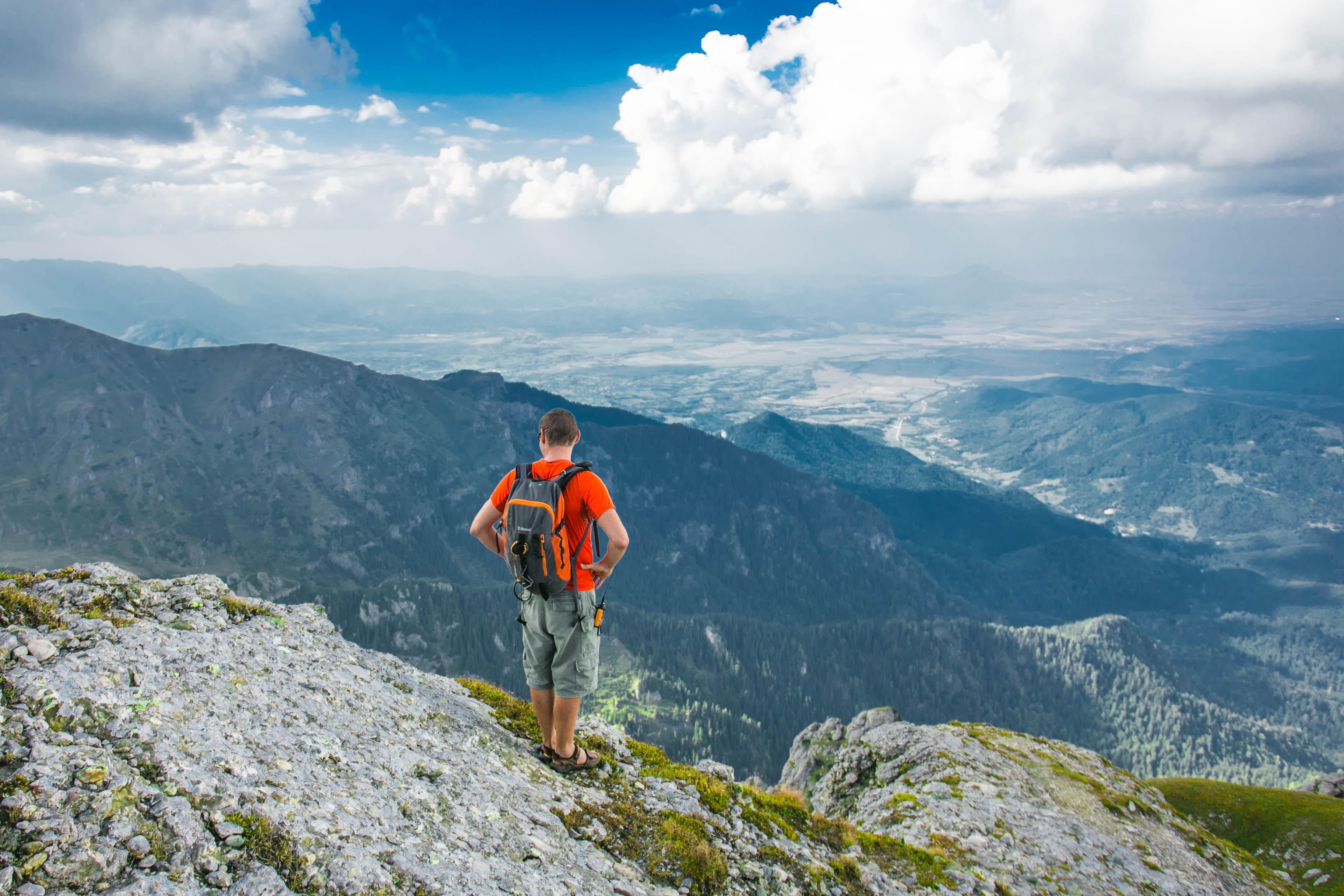 man standing on peak front of mountain at daytime