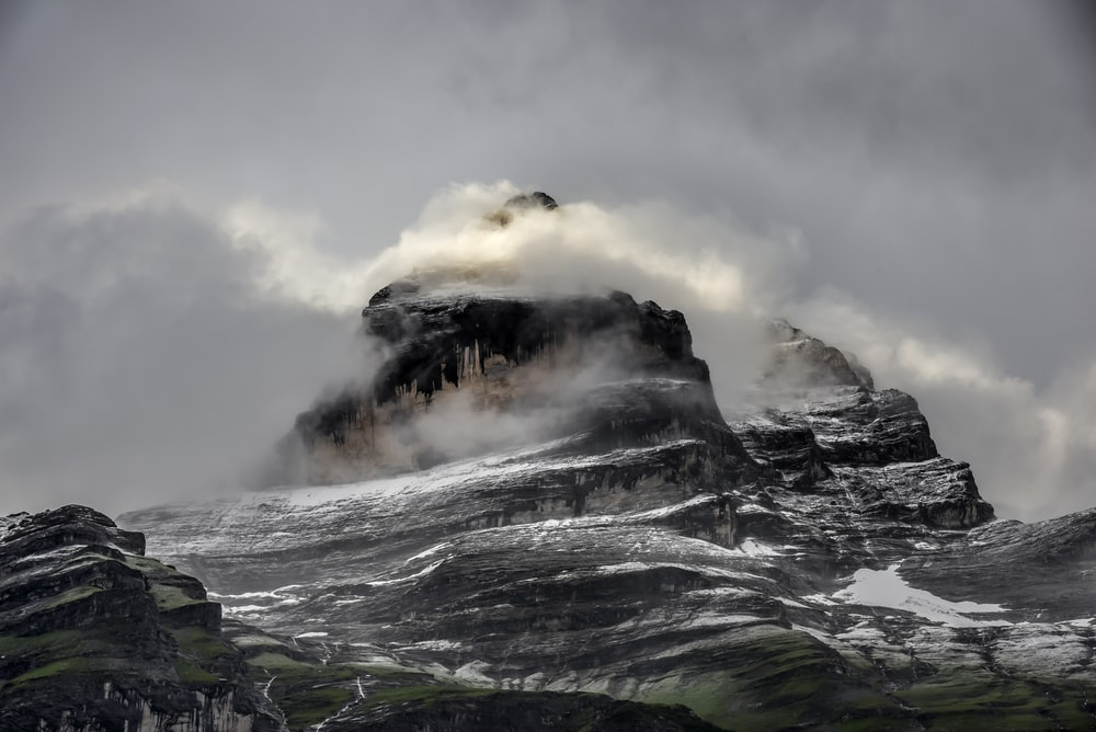 low angle photo of gray and black rugged mountain and clouds at daytime