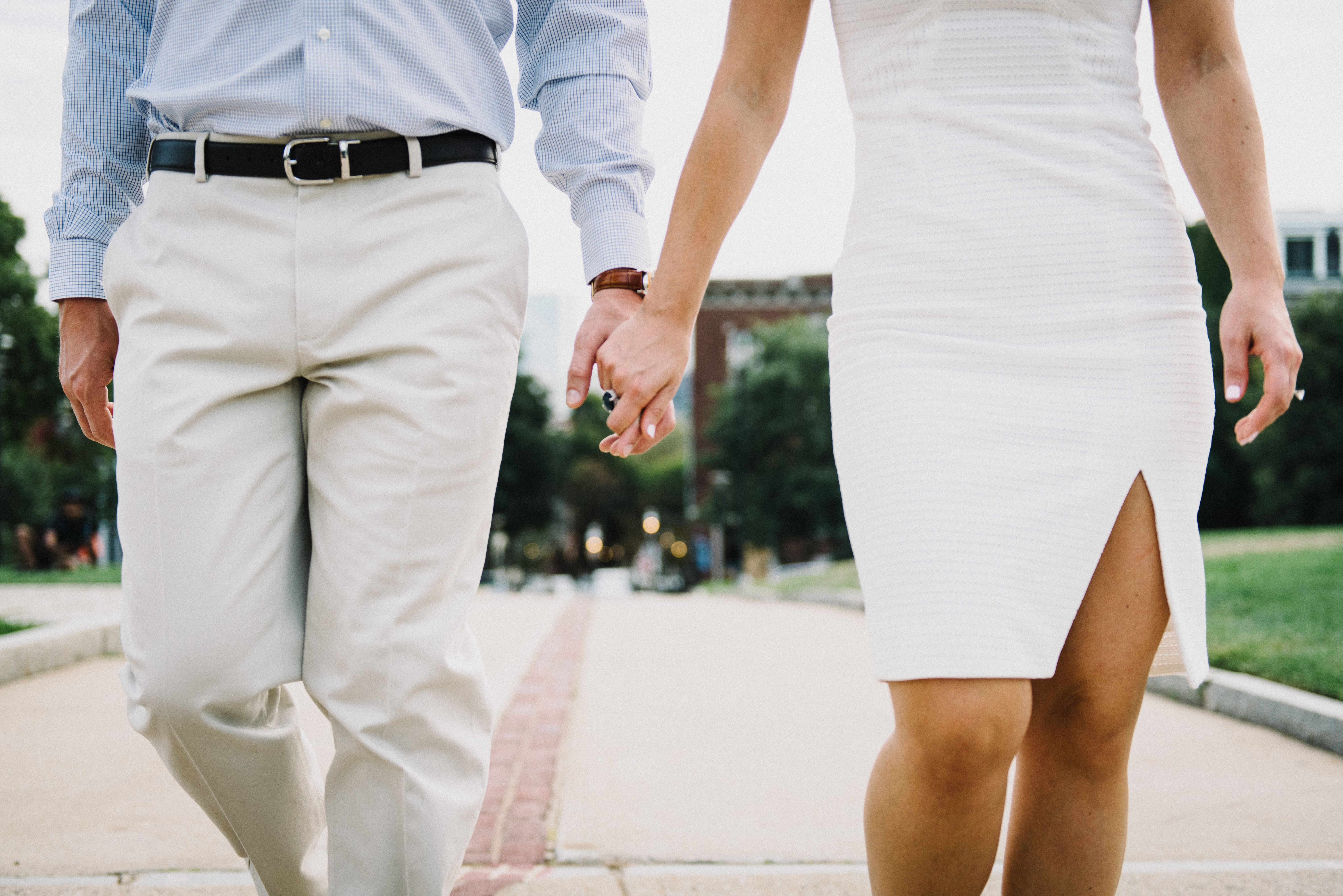 A dressed-up couple holds hands and strolls on a path through a Boston park