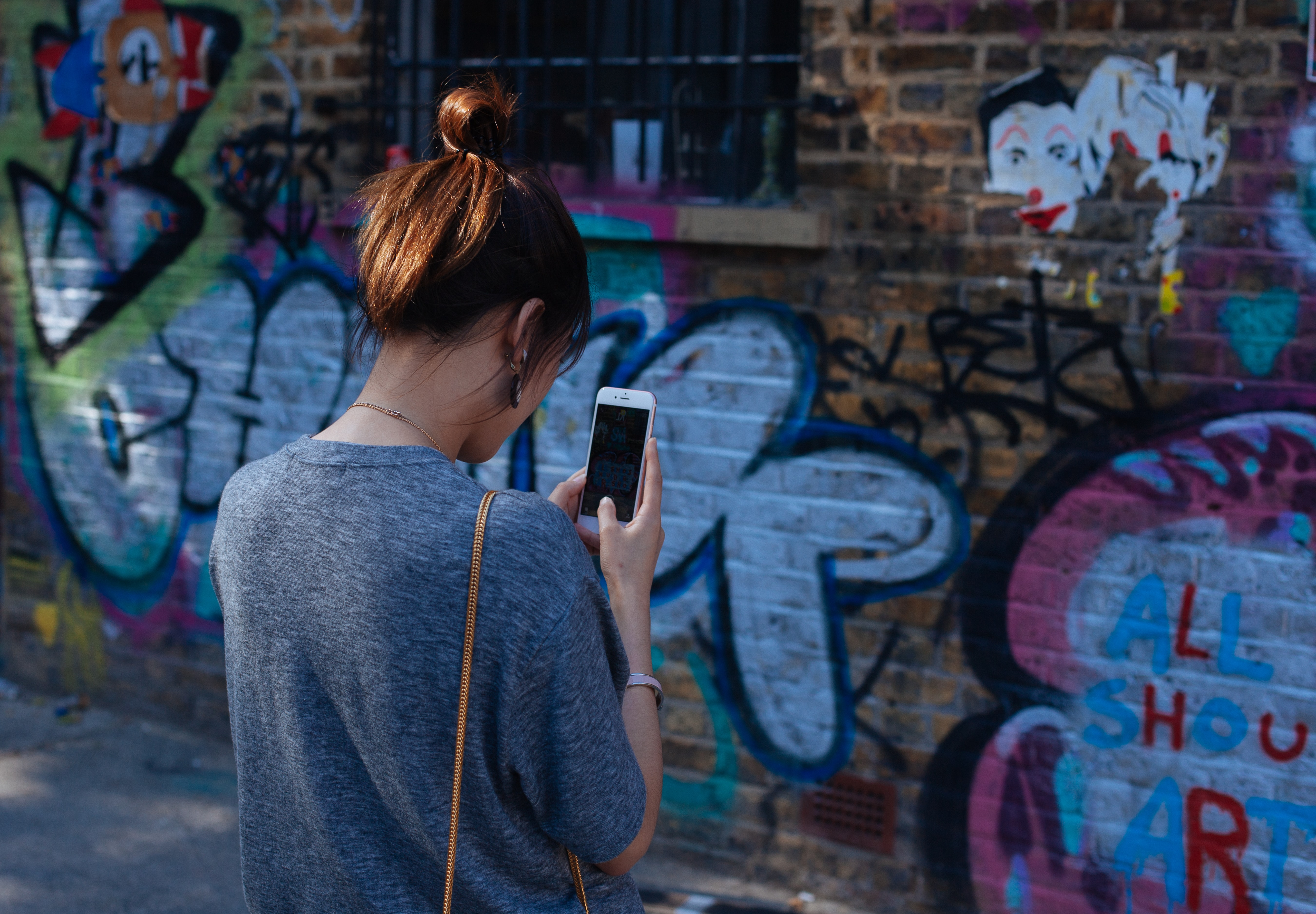 Young woman on iphone with grey jumper taking picture of graffiti on wall at Brick Lane