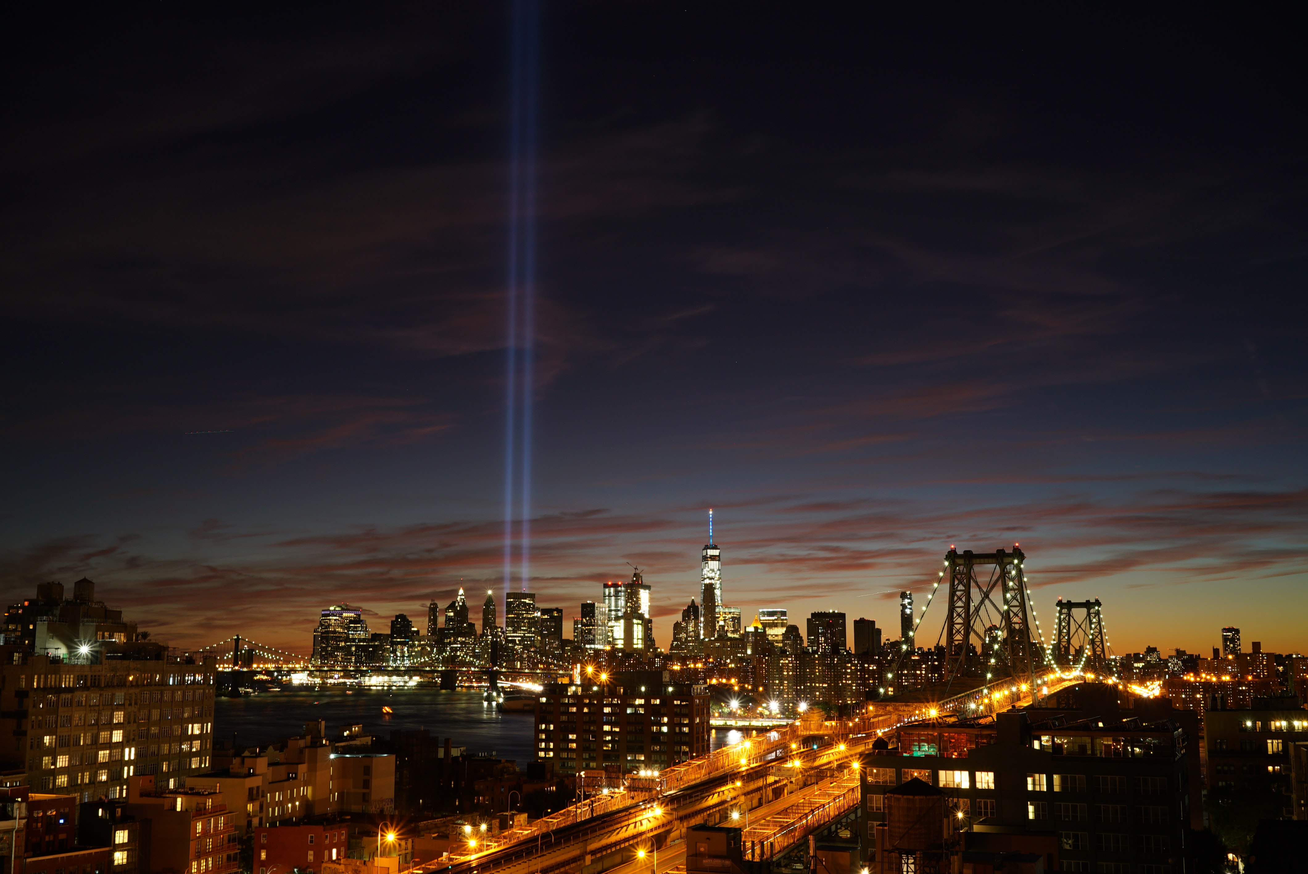 New York City's Brooklyn Bridge and city skyline with lights glowing at sunset