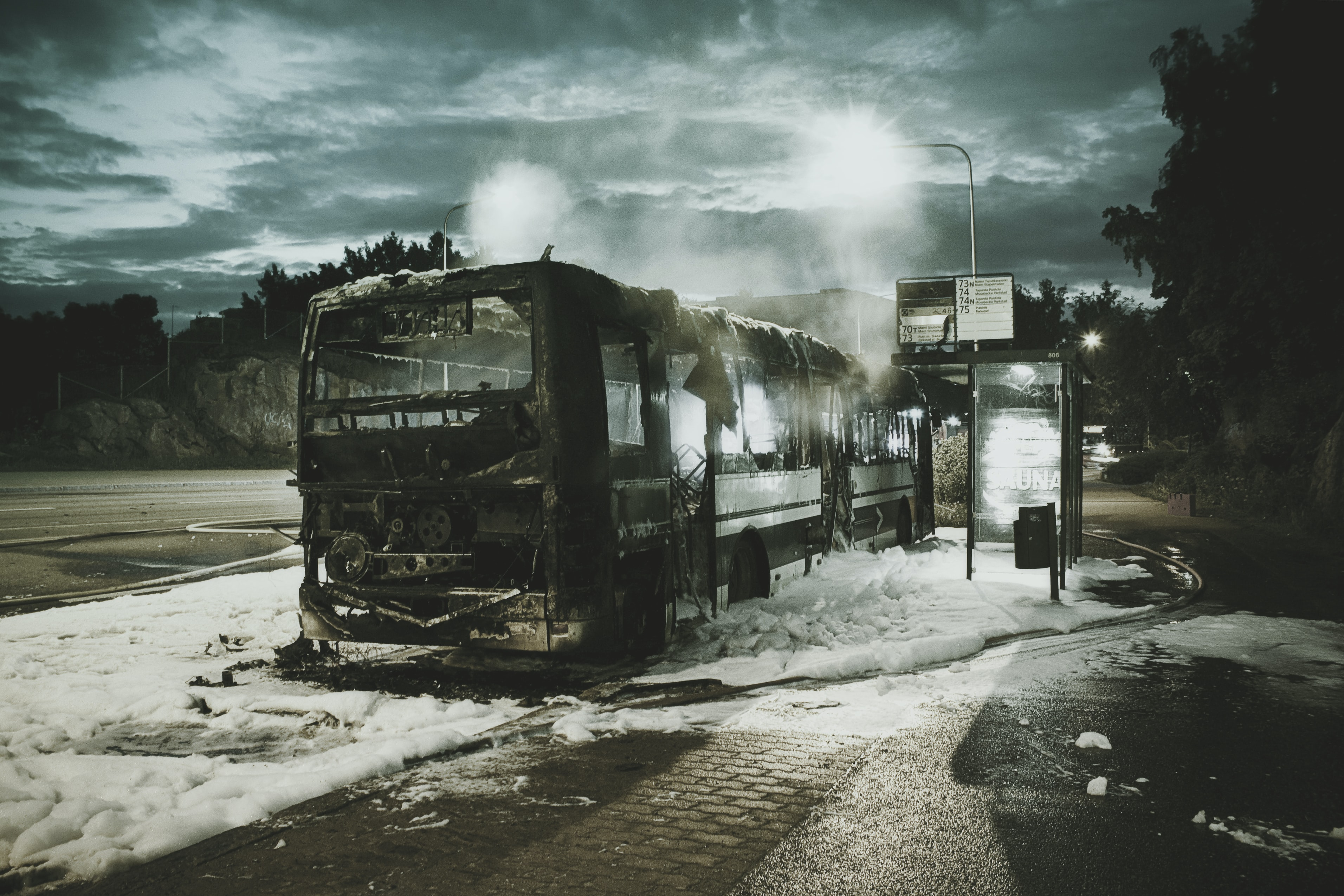 A burnt down bus on a patch of fire fighting foam next  to a bus stop