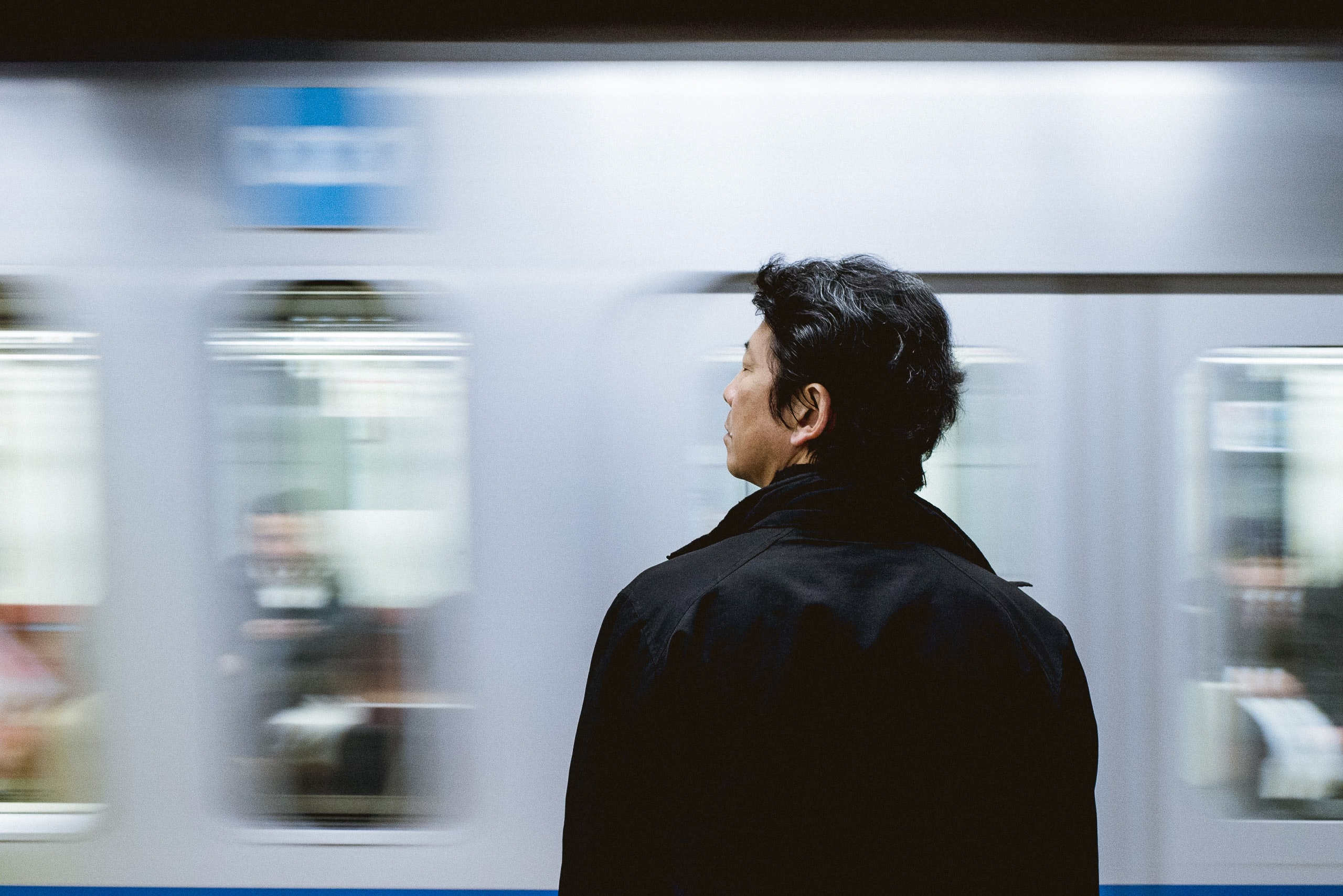 A man waits at the edge of the platform as a train arrives at the station
