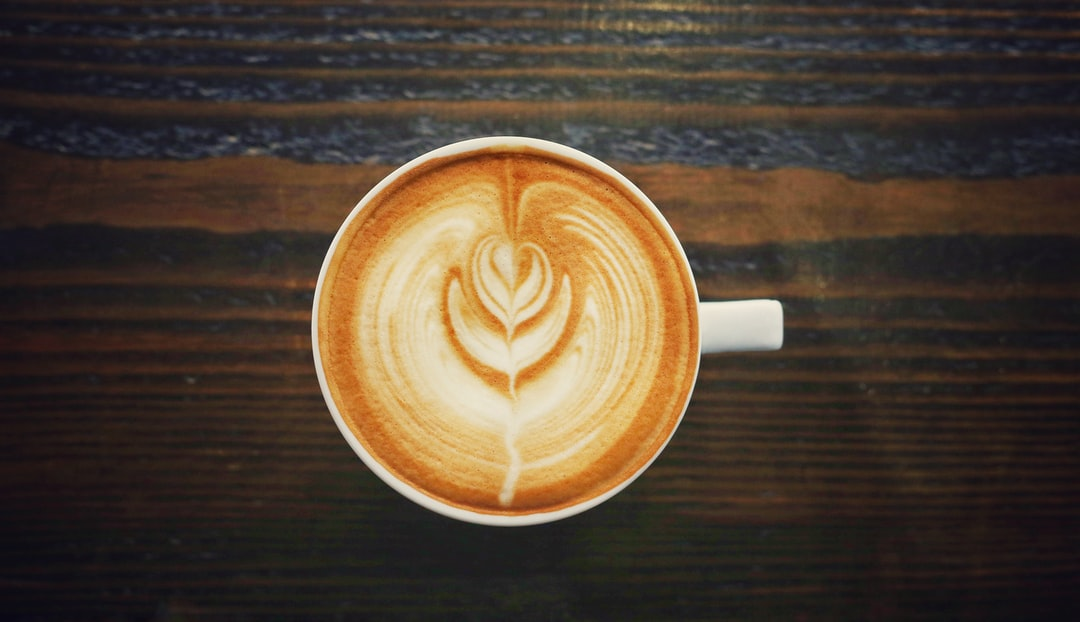 Cappuccino in a white mug with white foam art on a wooden table