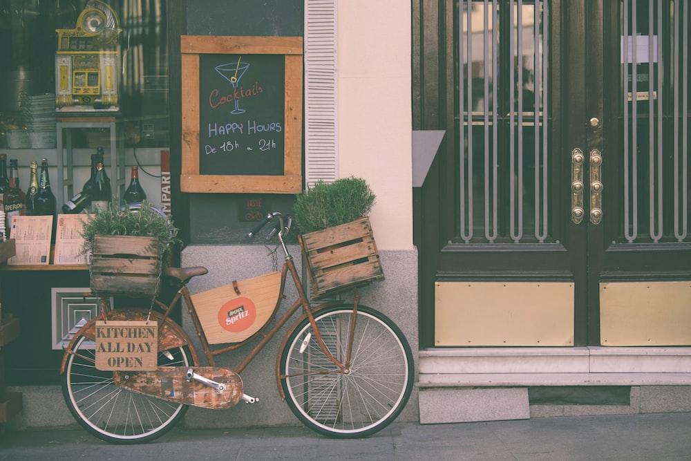 brown city bicycle near brown wooden door