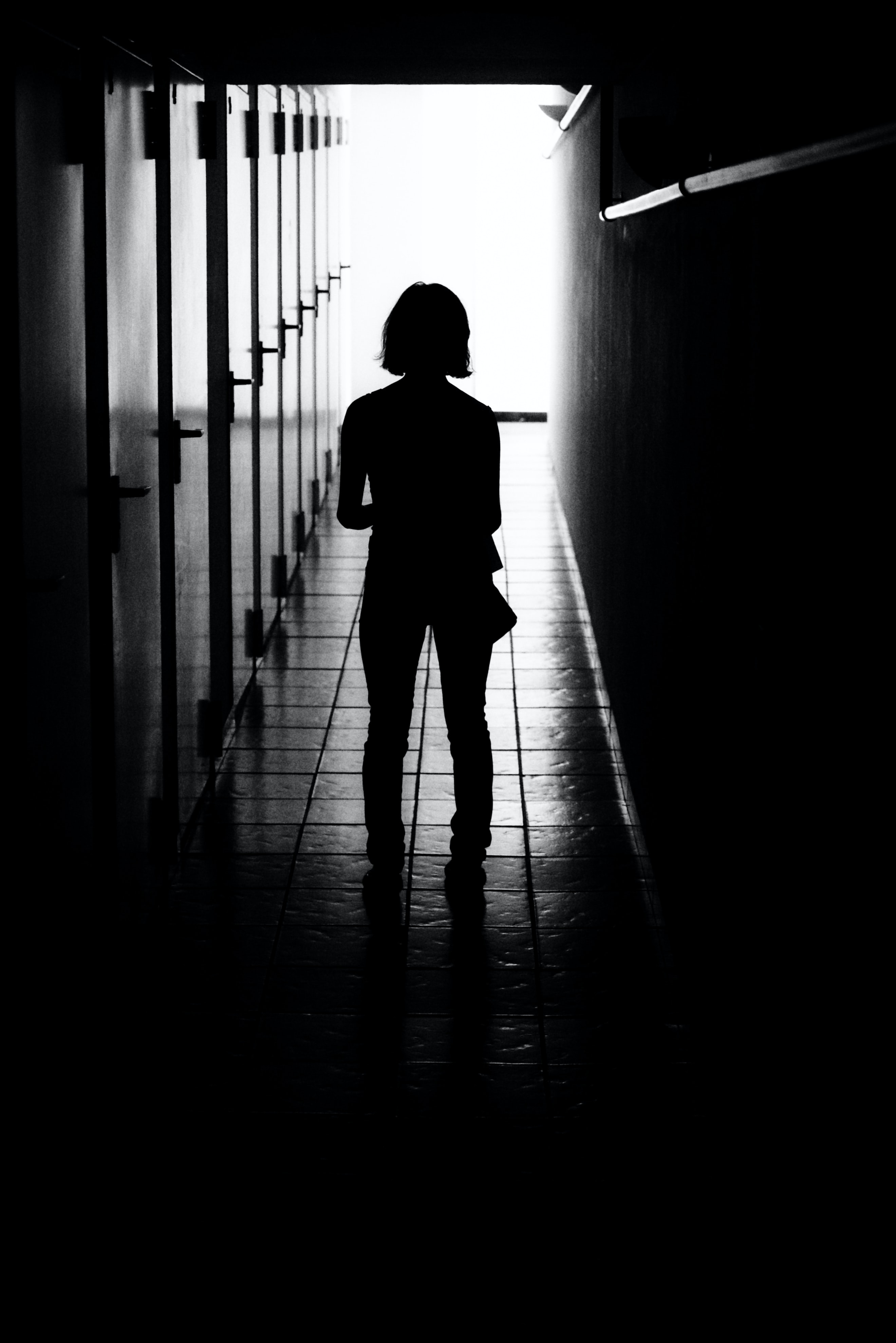 The silhouette of a female in a hallway, surrounded by darkness.