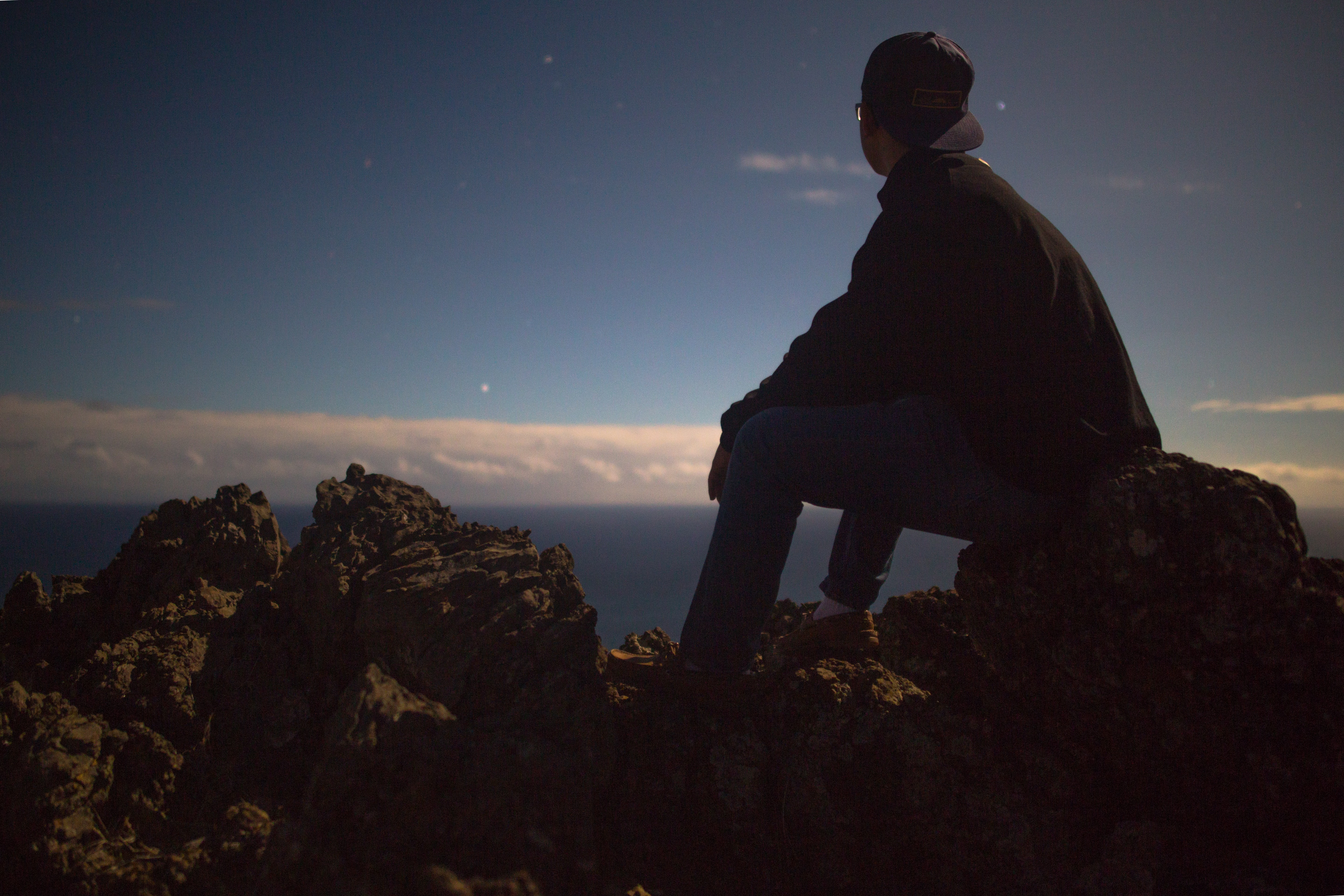 A man with glasses sitting on the rocks looking at the sea in the distance.