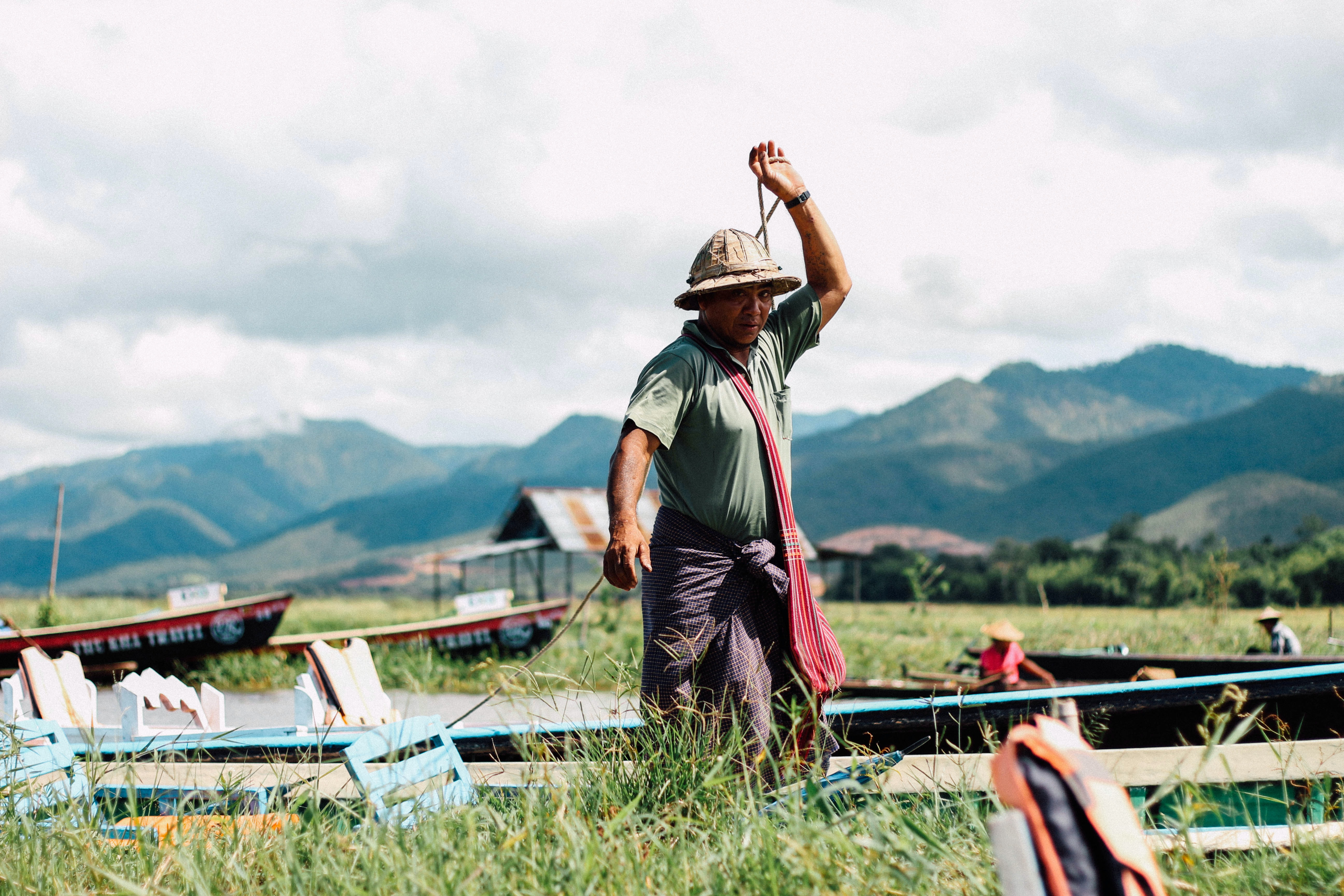 A fisherman wearing a hat preparing his fishing boat in Inle Lake