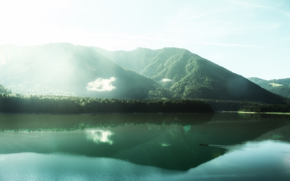 panoramic photography of boat on body of water near mountains at daytime