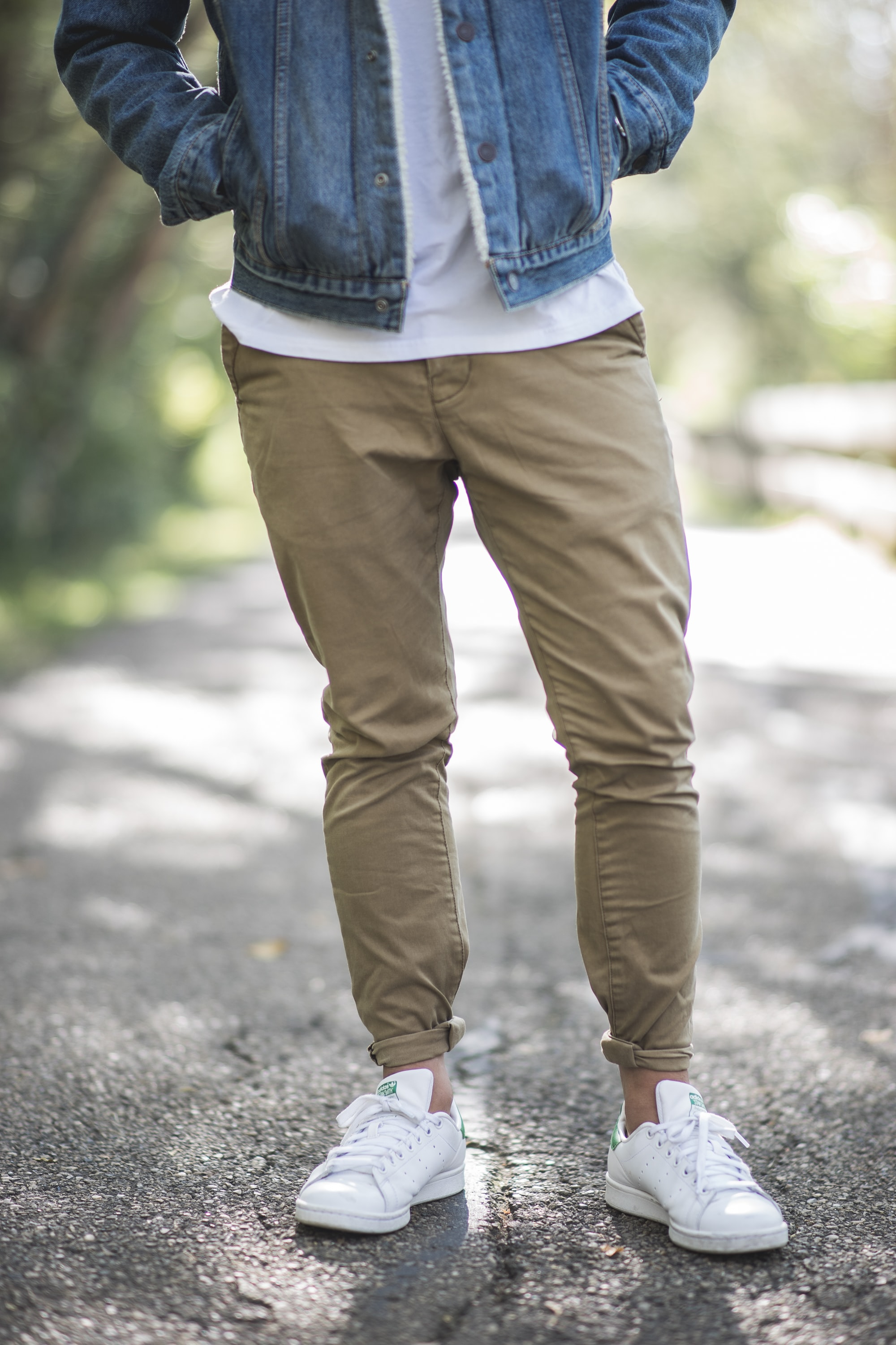 Low shot of a person in white sneakers, khakis, and a denim jacket