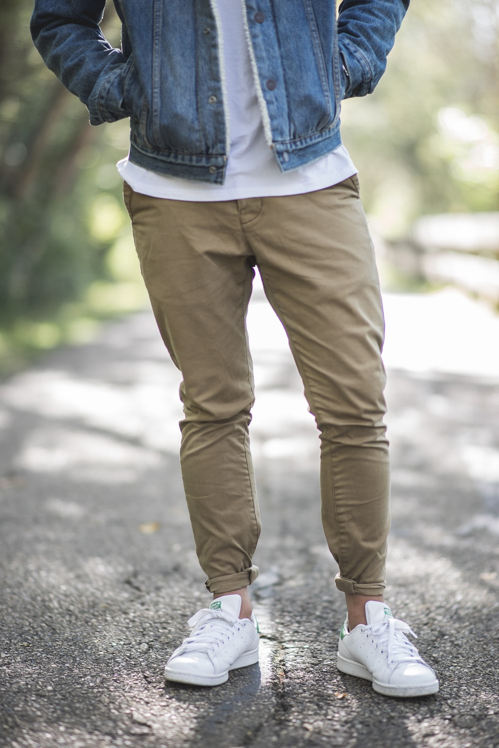 Man Wearing Brown Fitted Jeans And Sneakers Standing On Road At Daytime