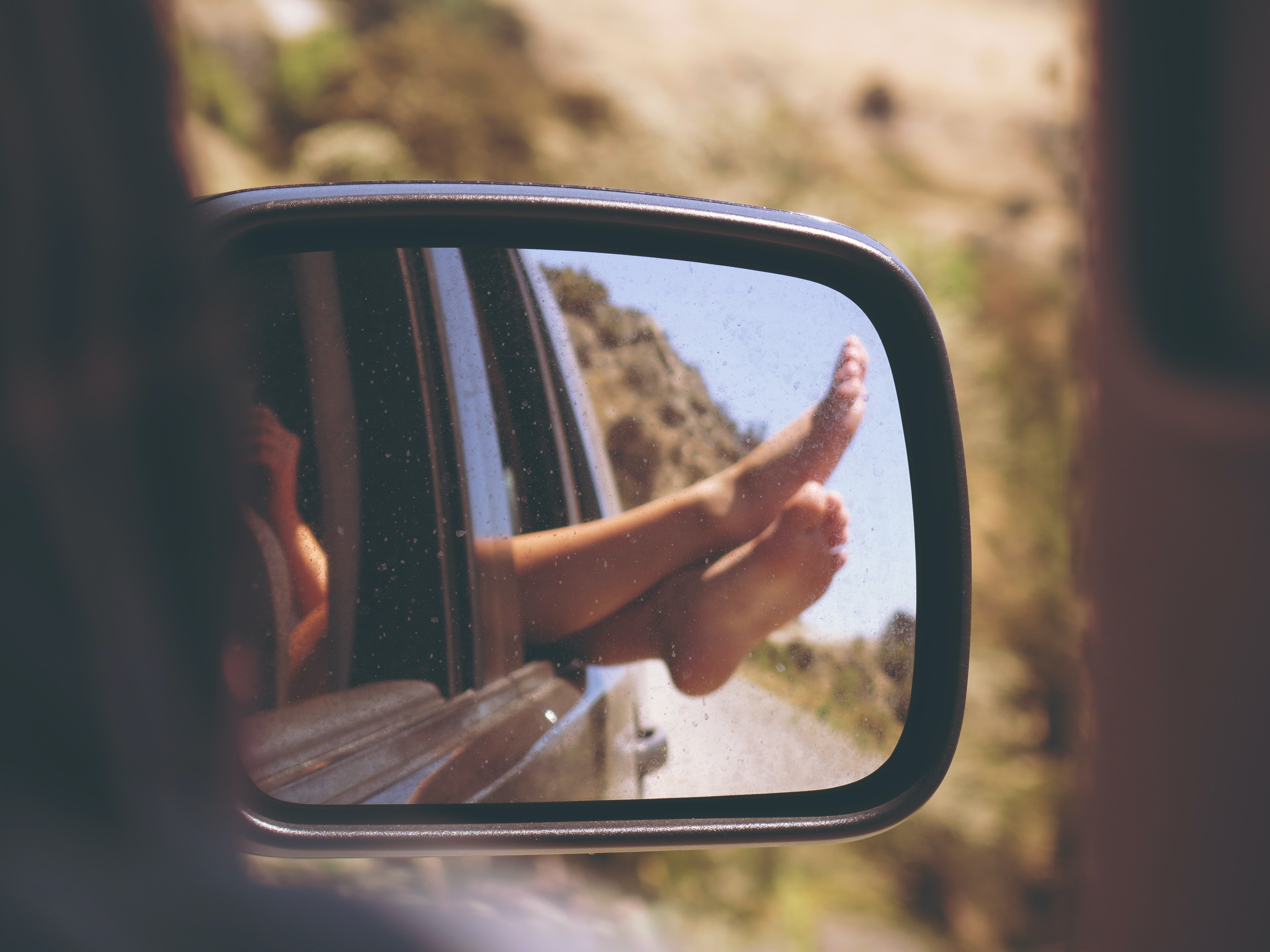 A person sticking their feet out of a car window from the perspective of the rear view mirror