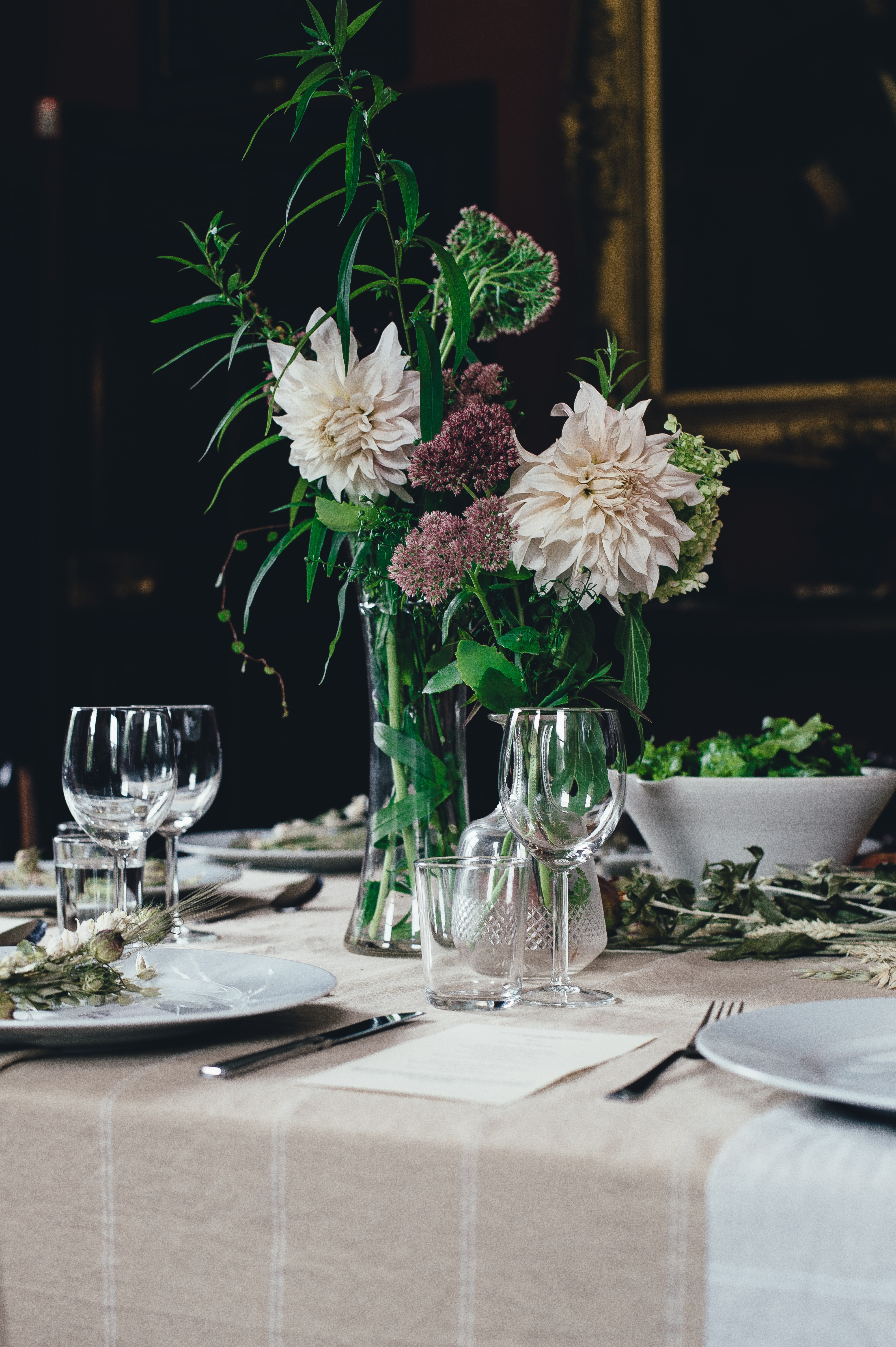 A set table with flowers in vases, empty plates and wine glasses