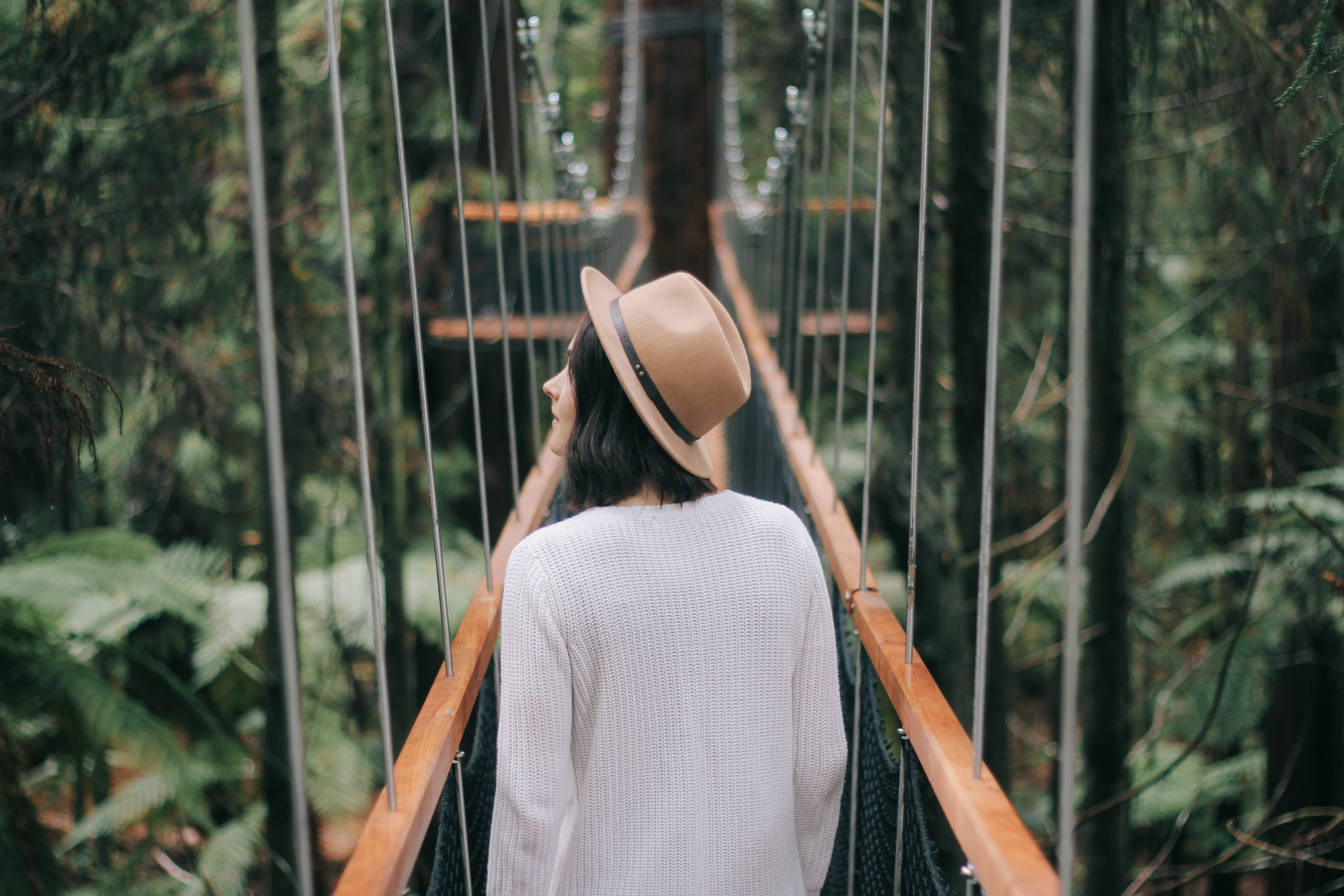 A woman wearing a hat and a sweater walking across a suspension bridge in the Redwoods forest