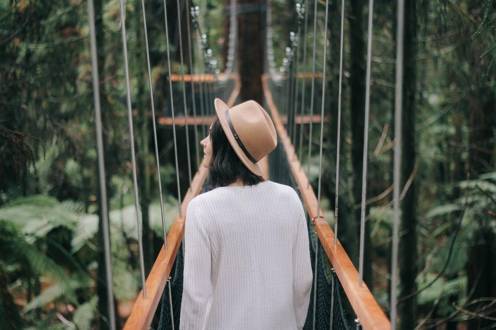 woman walking on bridge while looking around