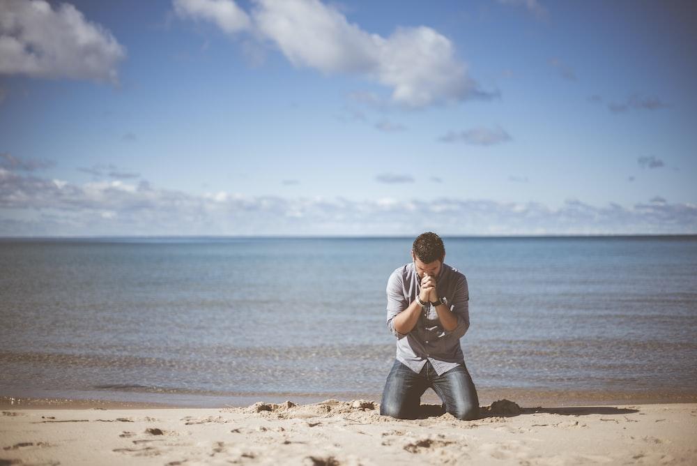 man kneeling down near shore