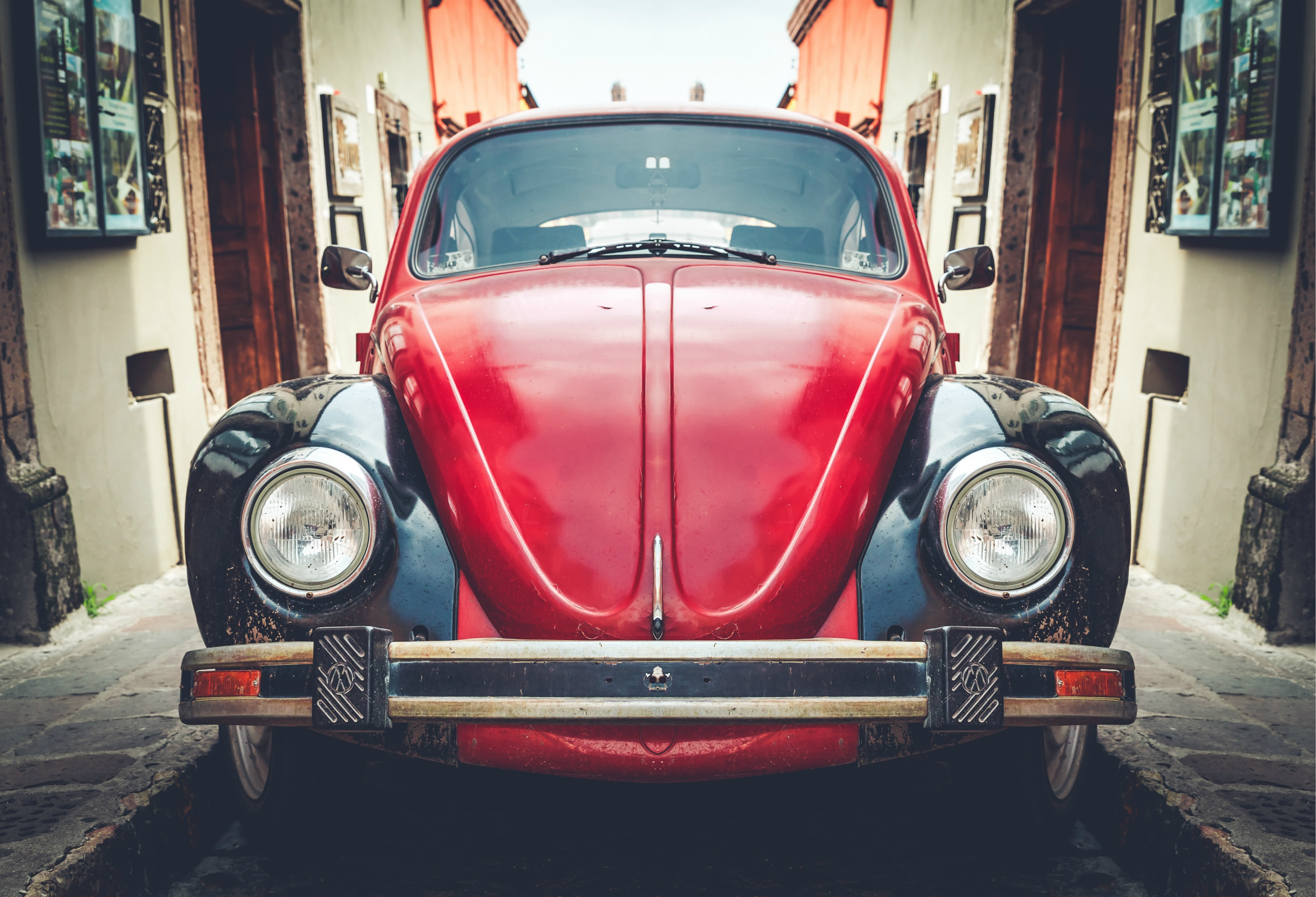 photo of red and black Volkswagen Beetle in alley