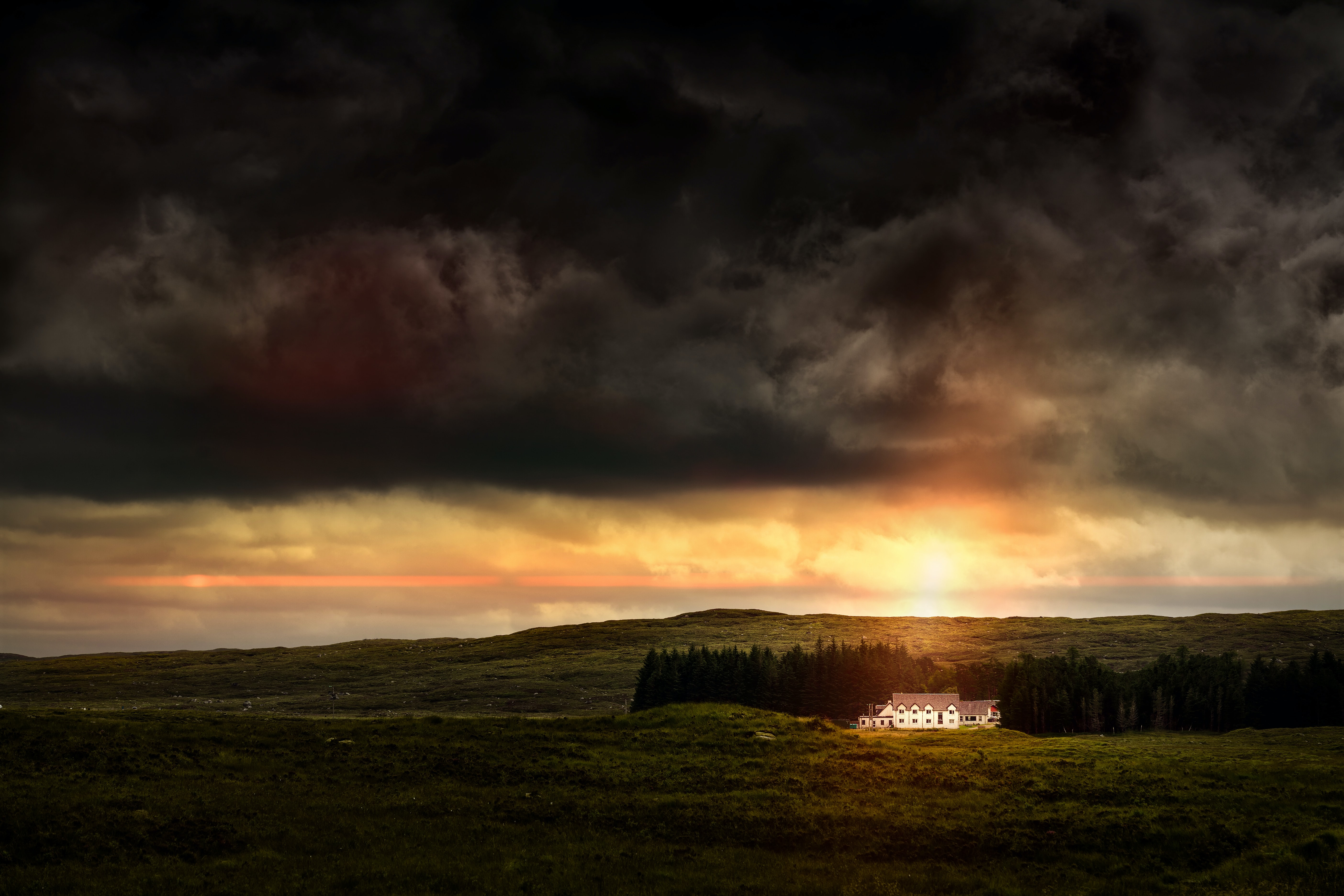 An elegant white building near a copse of trees during sunset in Glencoe