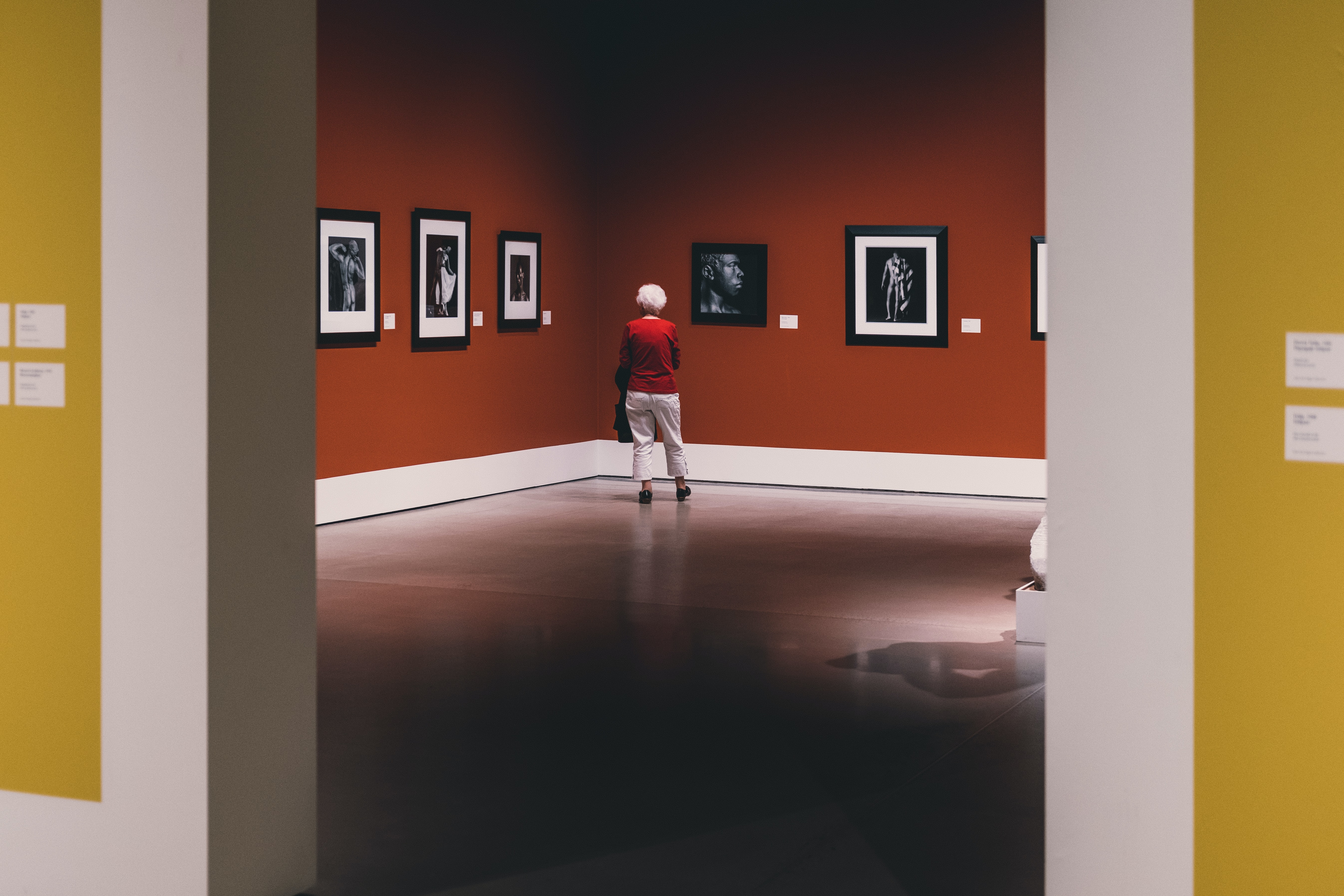 Older person in red jumper viewing artwork in gallery with marble floor and reflection