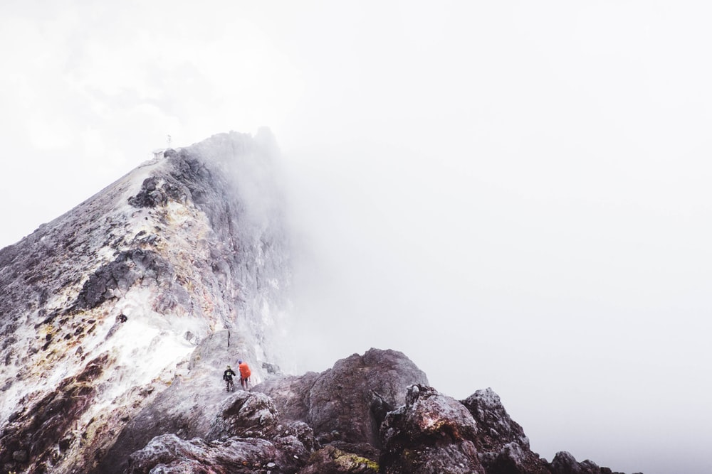 two people standing on mountain slightly covered with fogs during daytime
