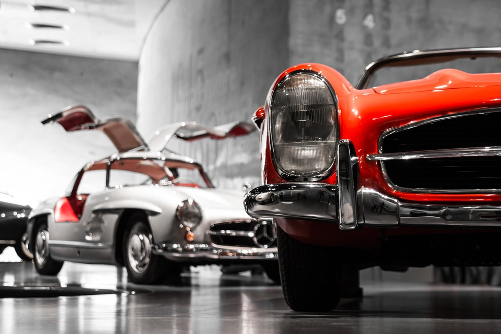 two vintage cars beside gray concrete wall