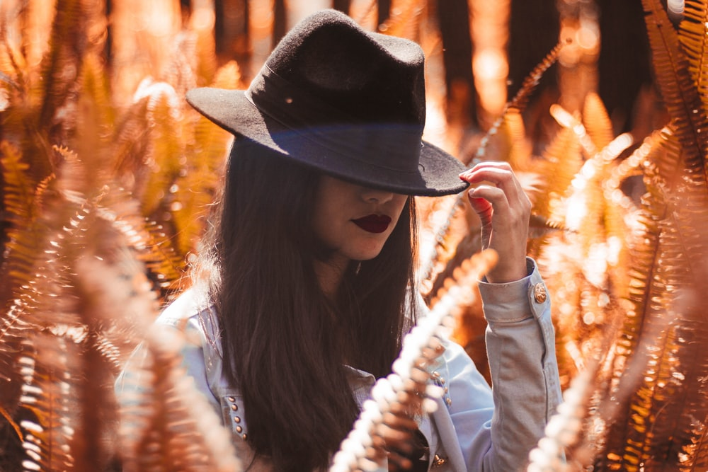 photography of woman in white long-sleeved top holding black bucket hat
