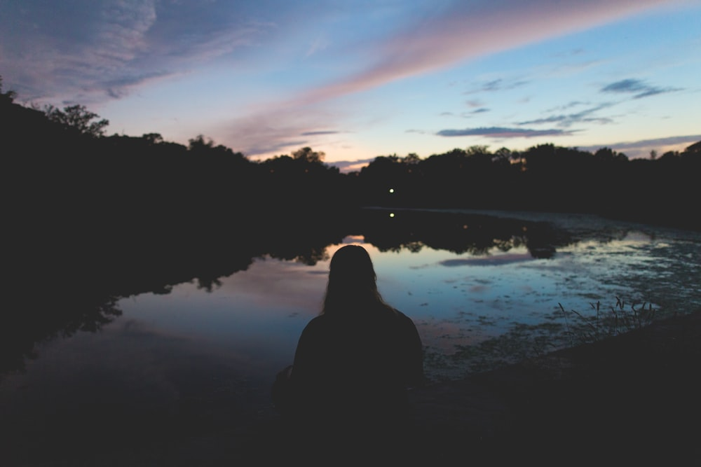 silhouette of person sitting near body of water