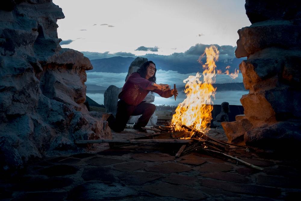 person kneeling in front of bonfire outside
