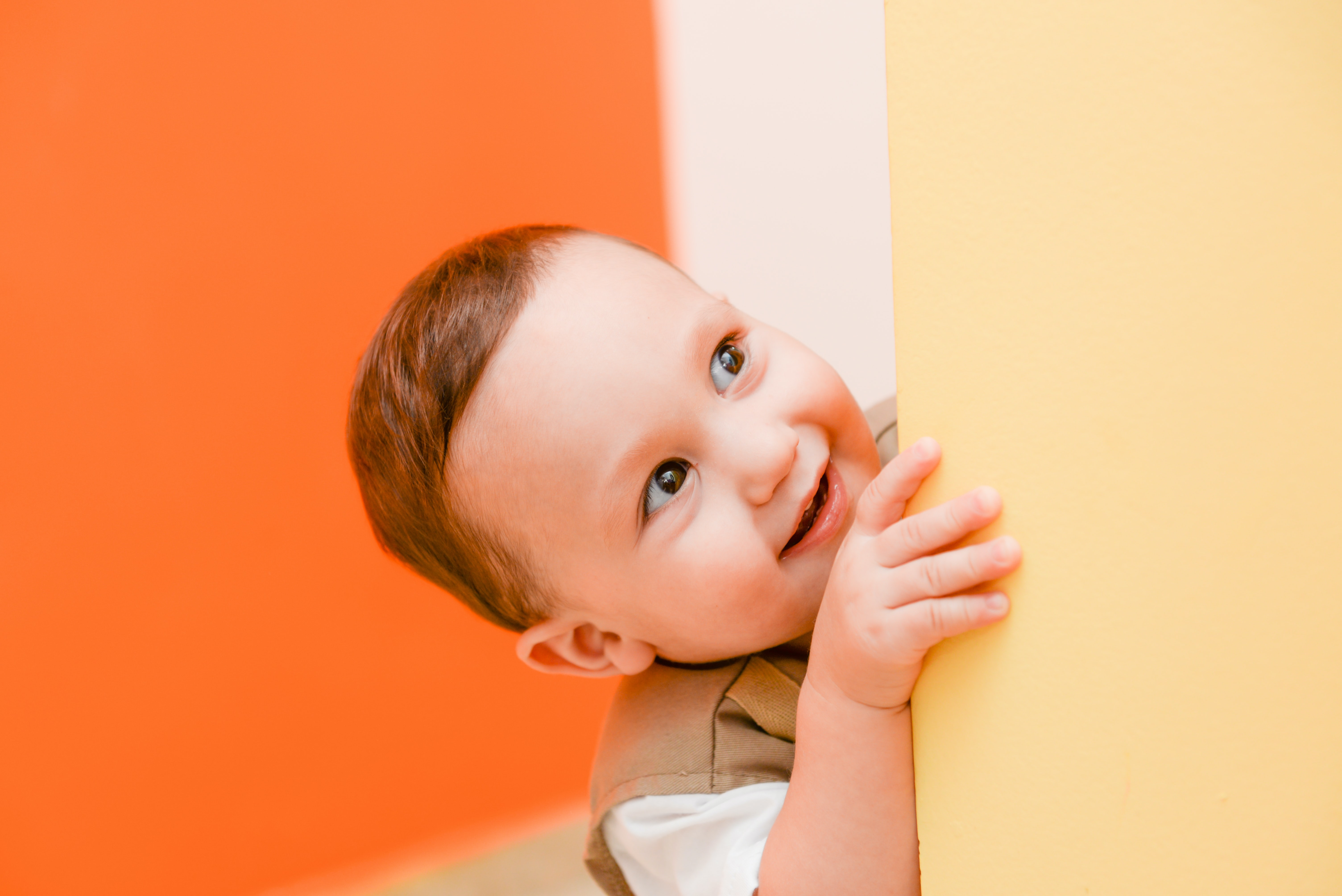 baby hiding beside beige wall