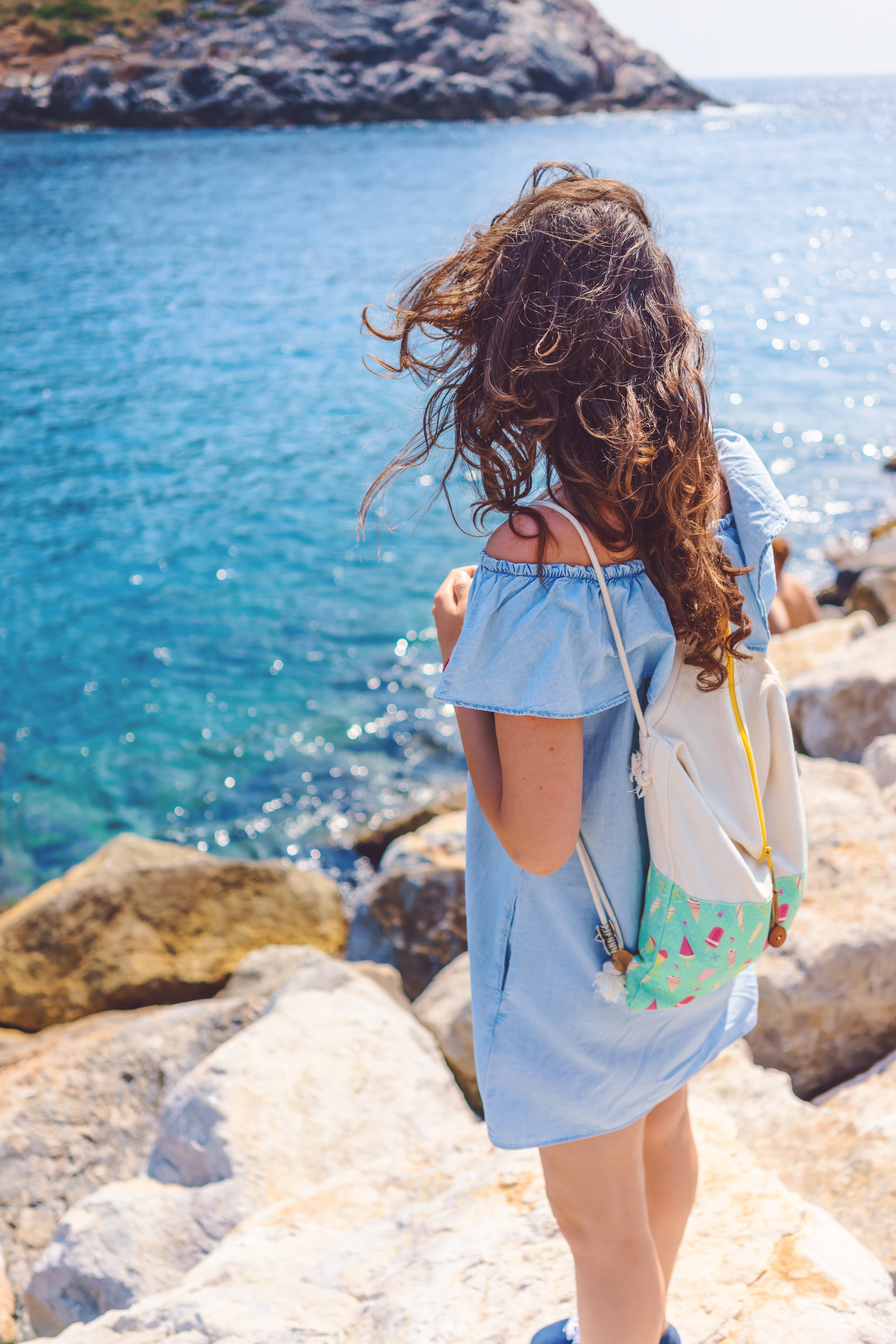 Woman with a drawstring bag standing on a rocky sea shore