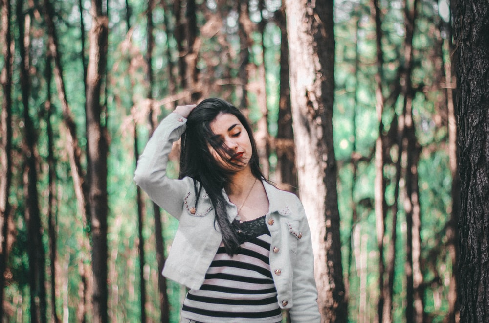 A young woman brushing back her hair in a forest