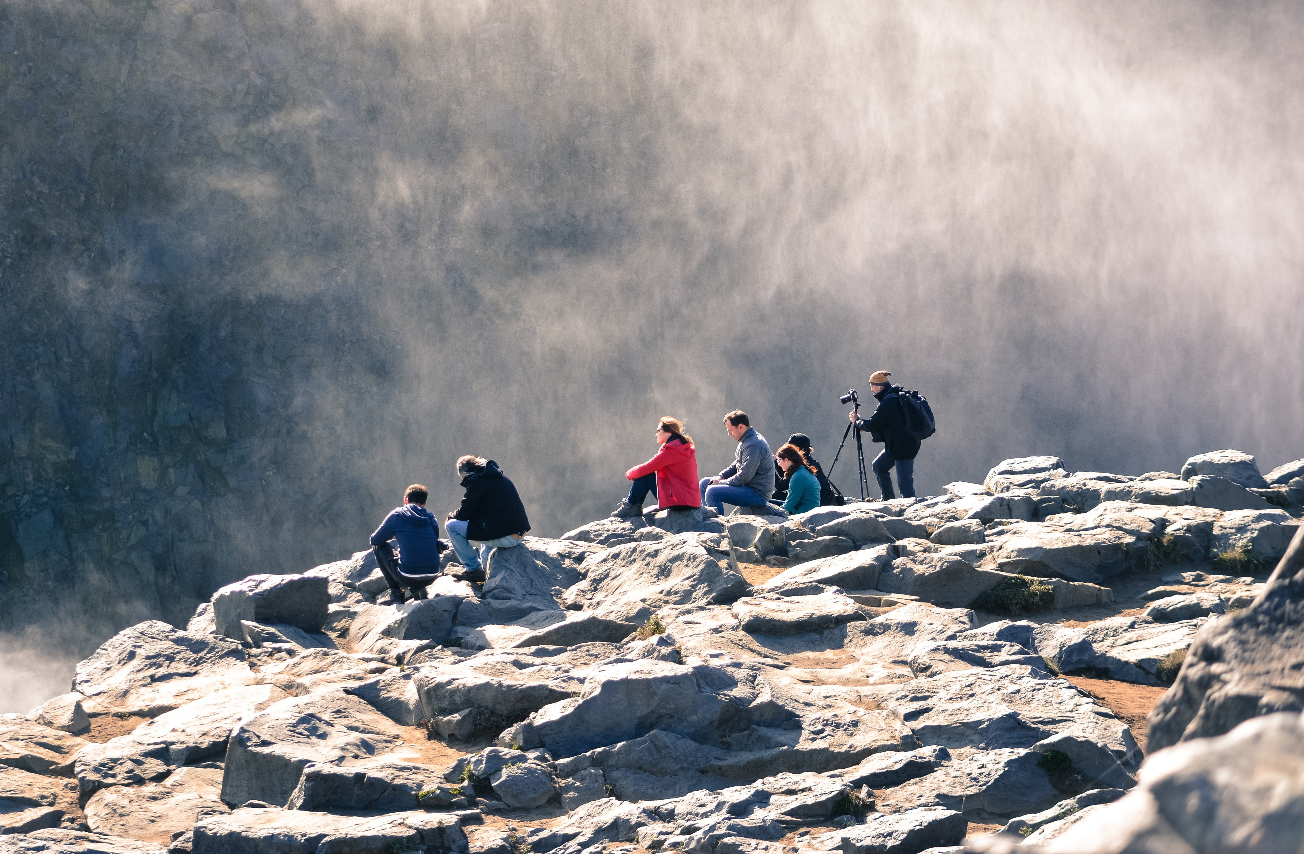 Group of adventurers resting on rocks, admiring and photographing the beauty of a mountain mist