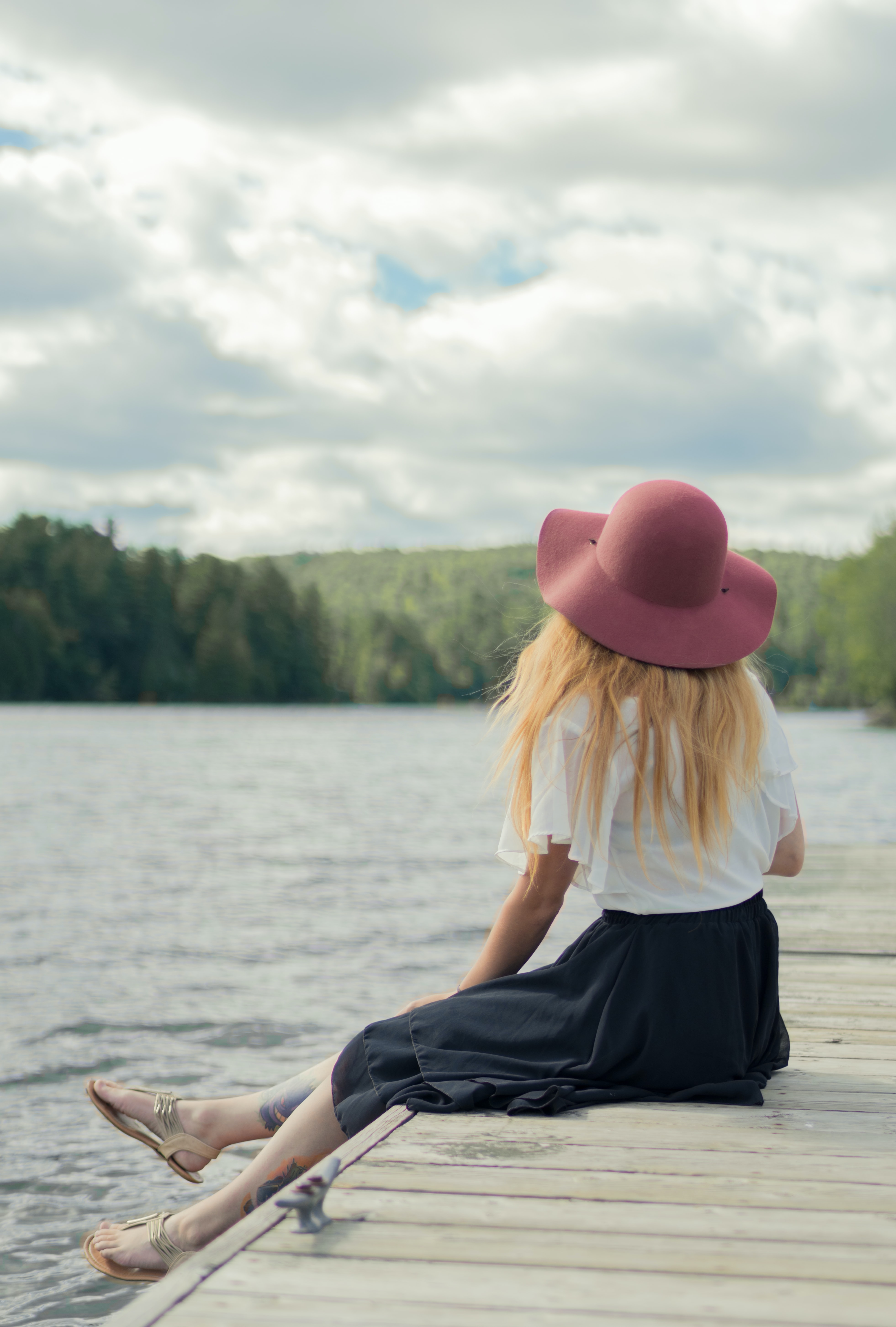 woman sitting on dock under cumulus clouds