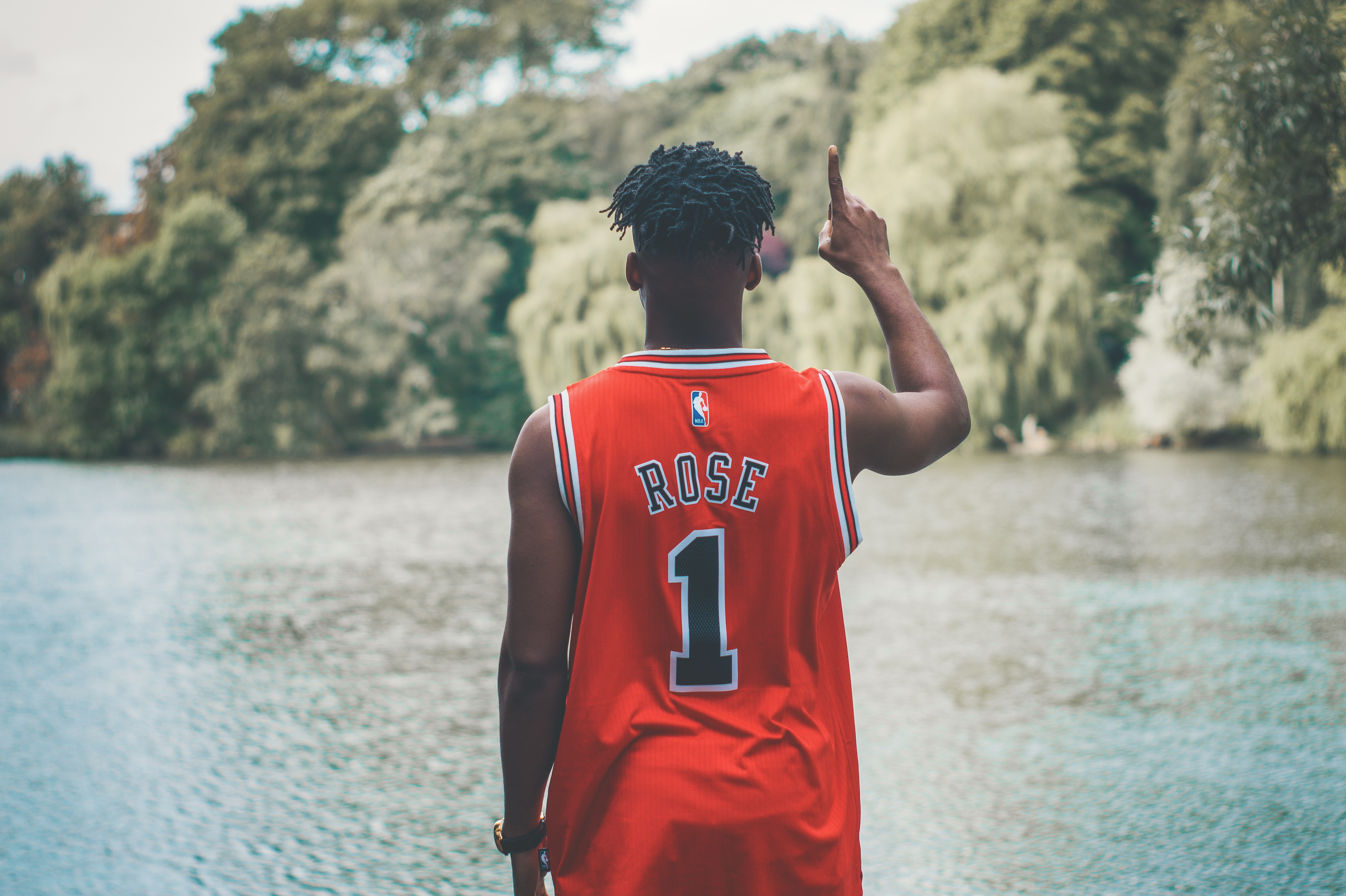 Man in Derrick Rose jersey holding his index finger up while staring out into a lake