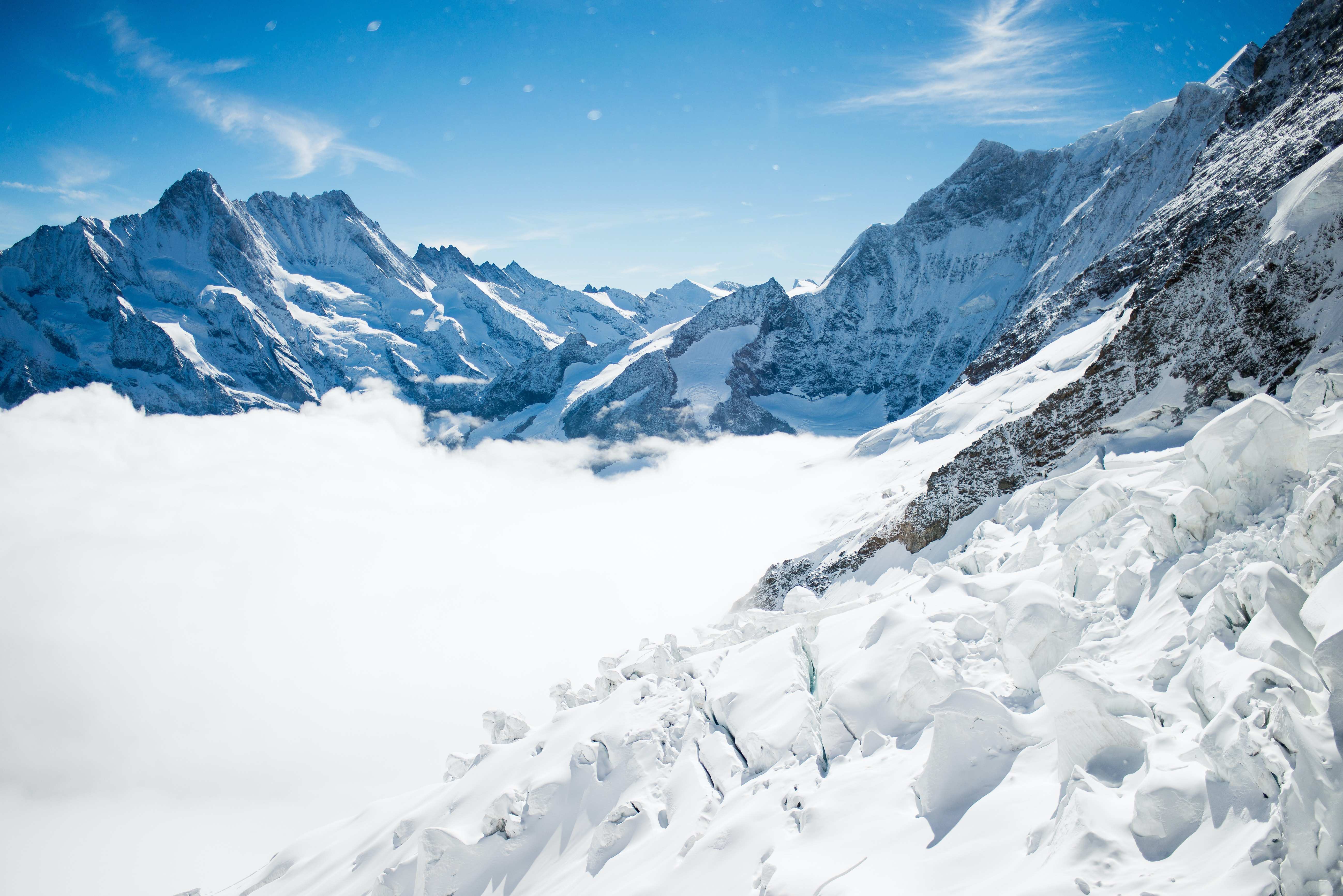 Snowy plain surrounded by snow covered mountains with a bright blue sky