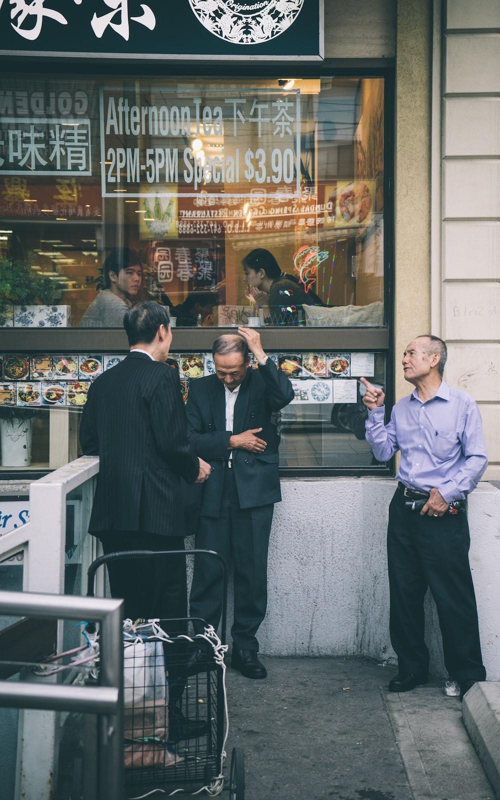 three men standing beside building