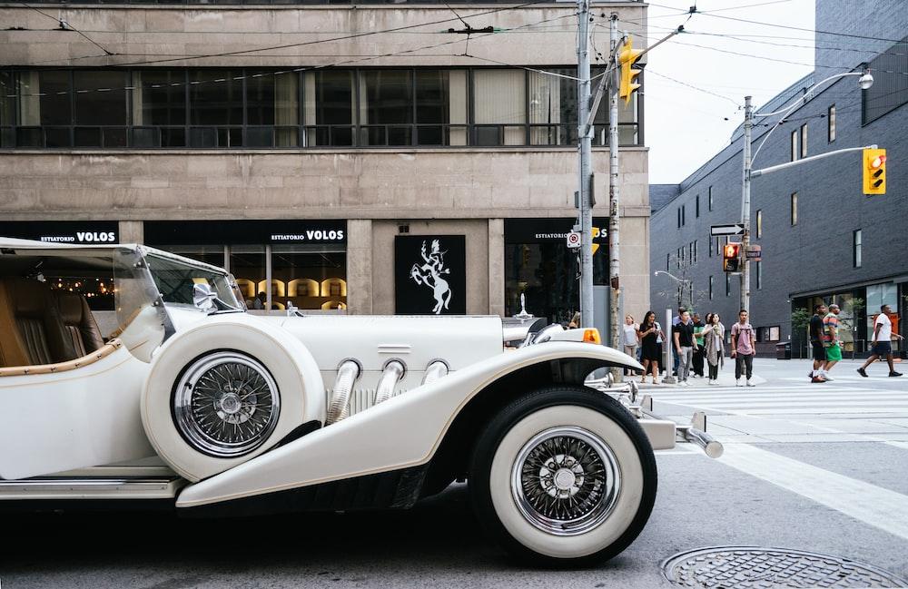 photo of classic white vehicle near pedestrian lane