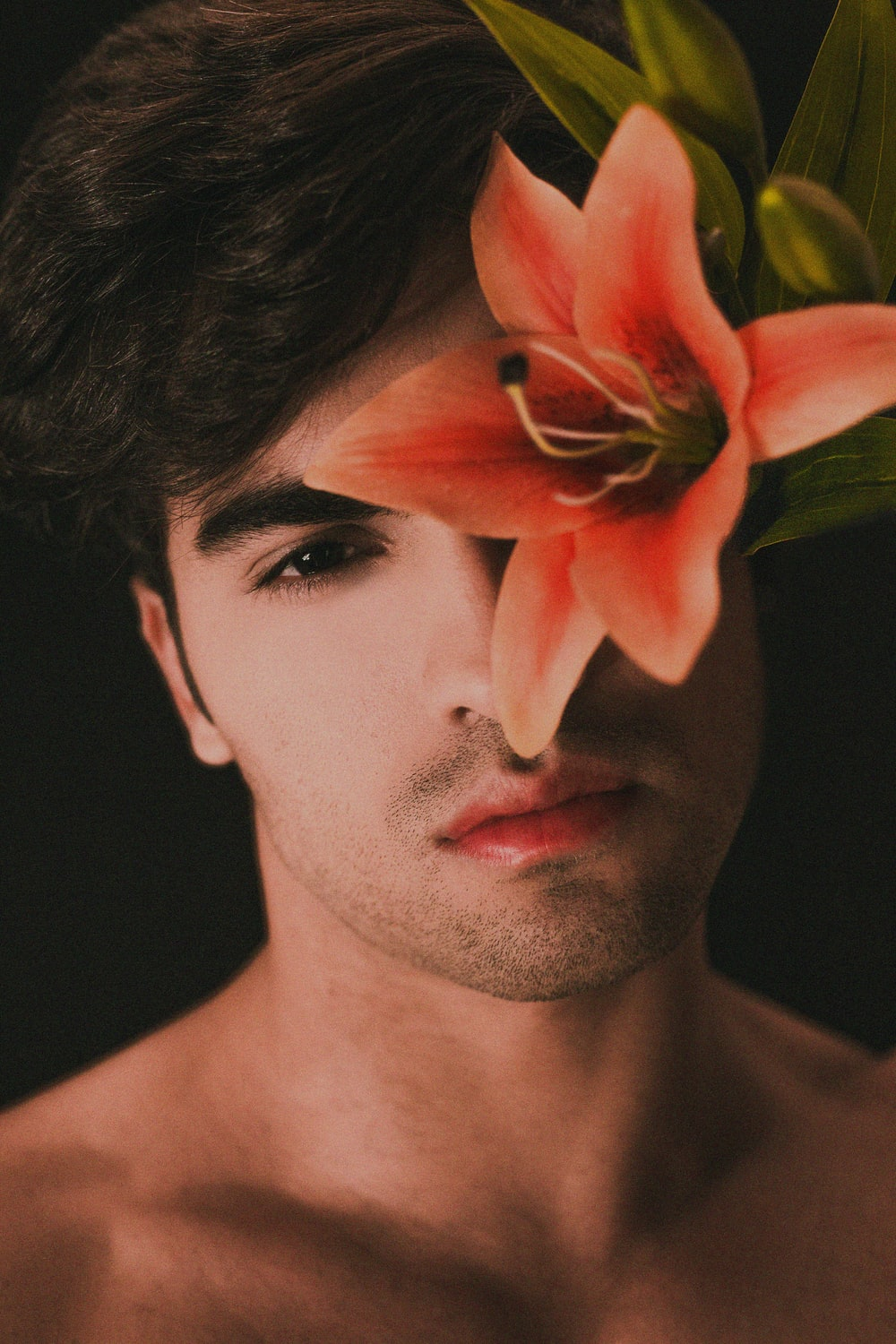 topless man with pink flower on ear