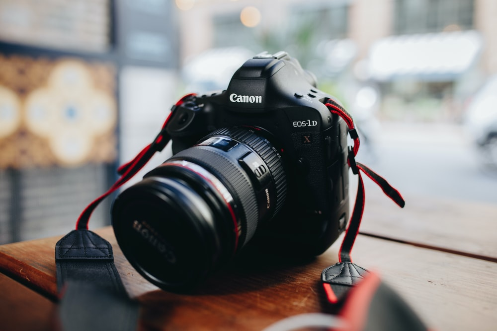 A Long Lens Canon Camera On Wooden Surface