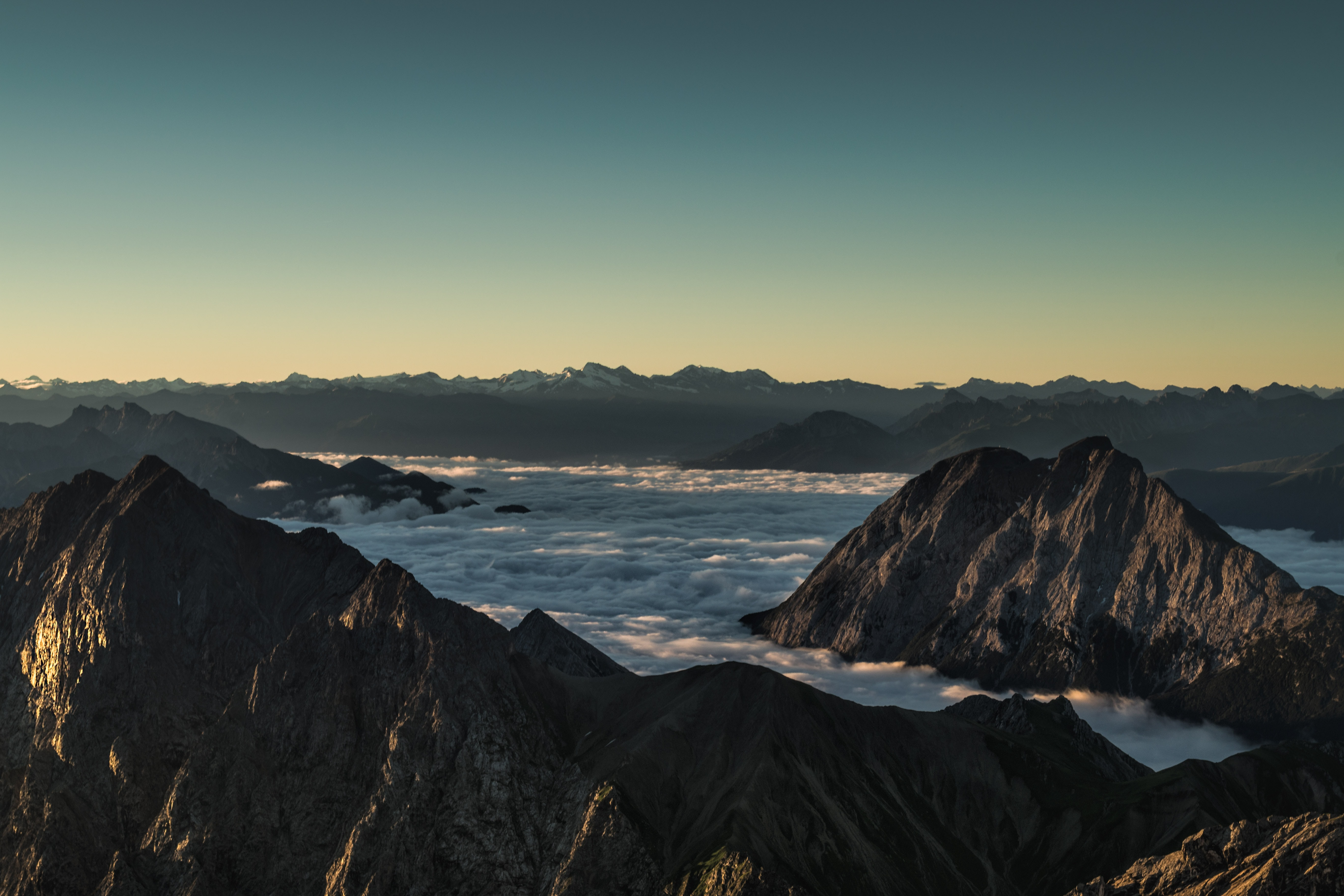 Craggy mountains rising up above clouds during sunrise