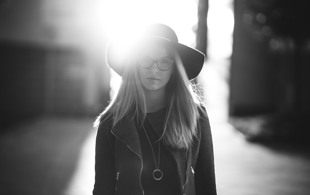 grayscale photography of woman wearing hat and coat standing near wall