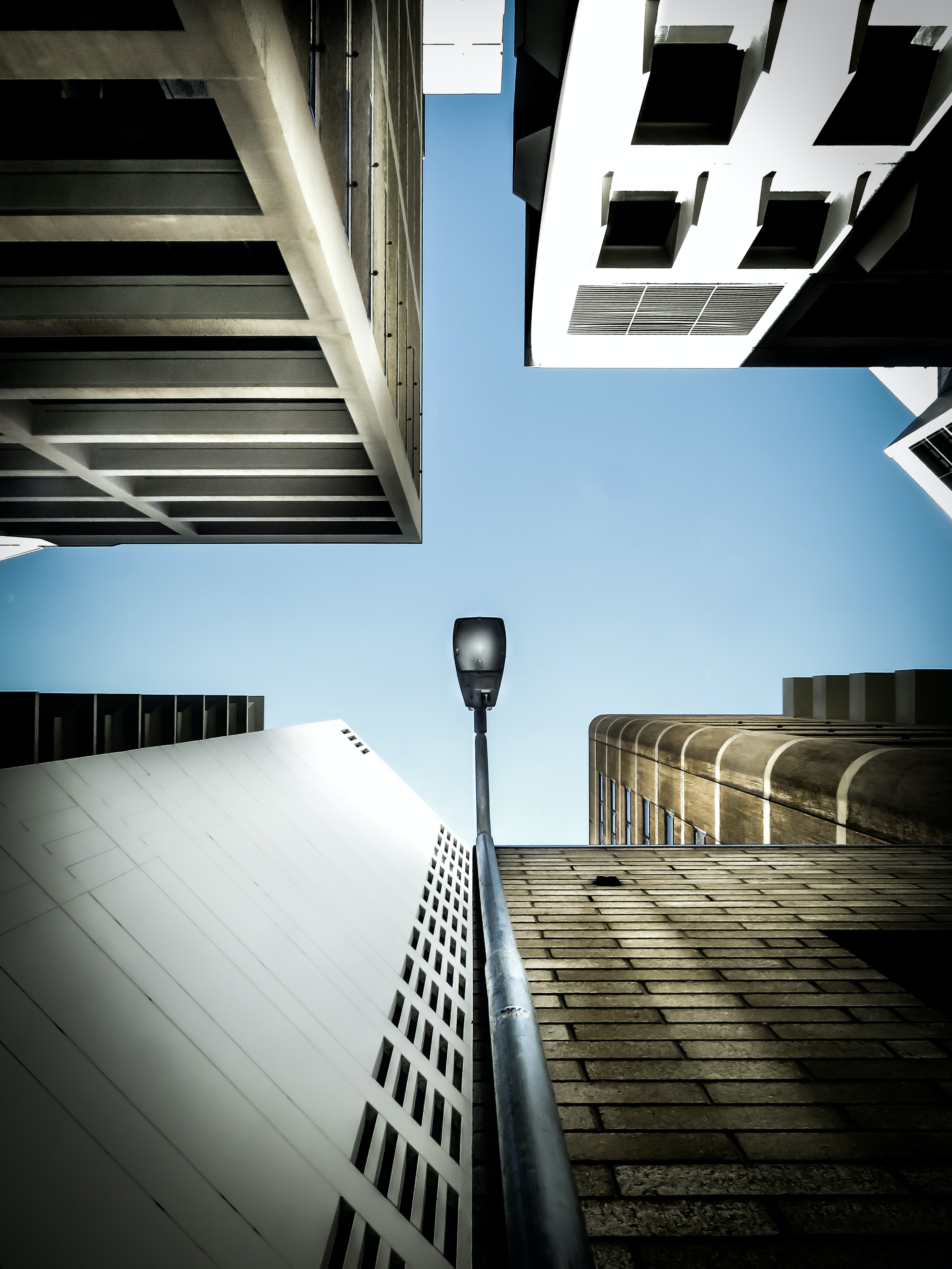 A low-angle shot of a lamppost adjacent to a building facade