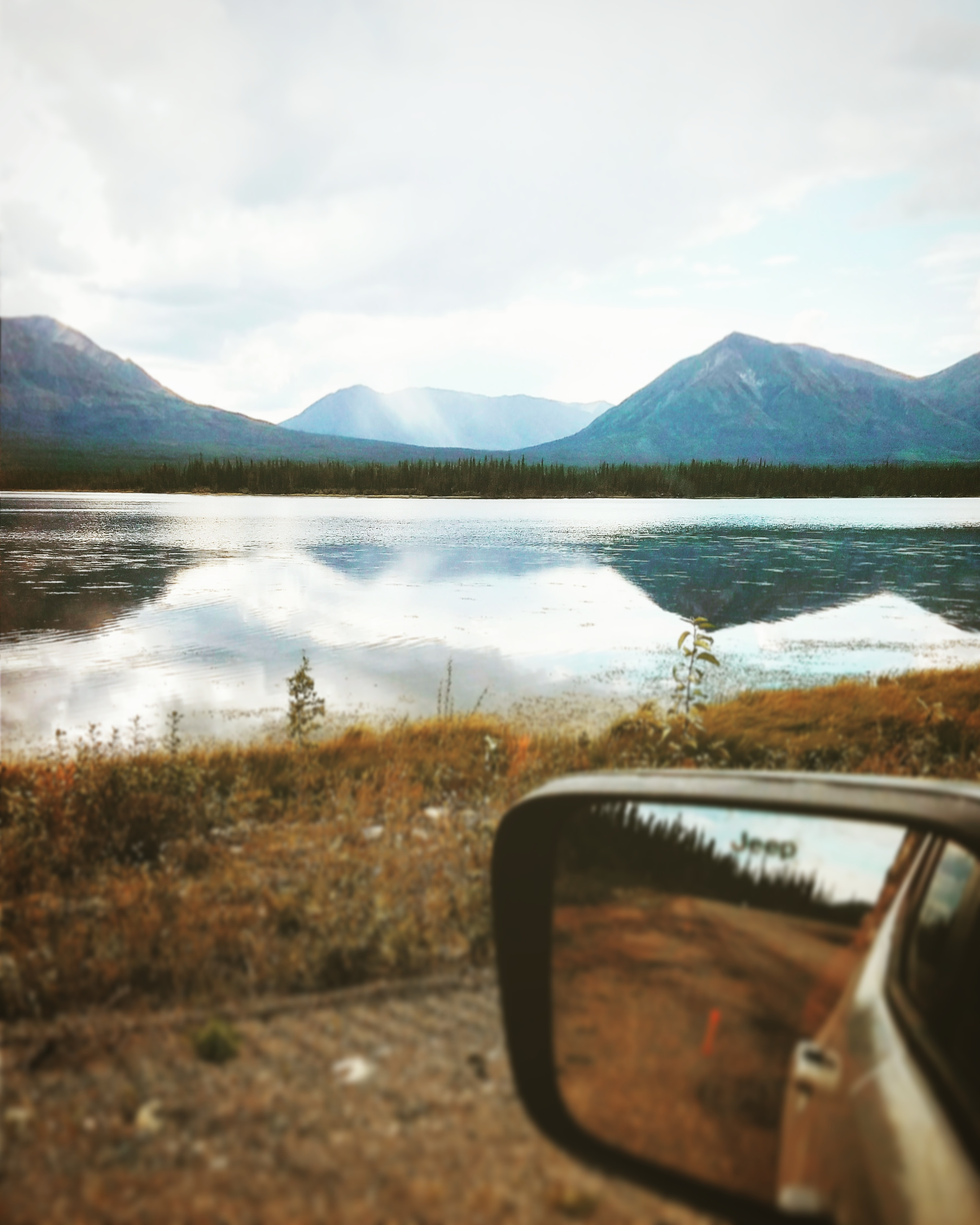depth photography of car side mirror with a scene of body of water near mountains