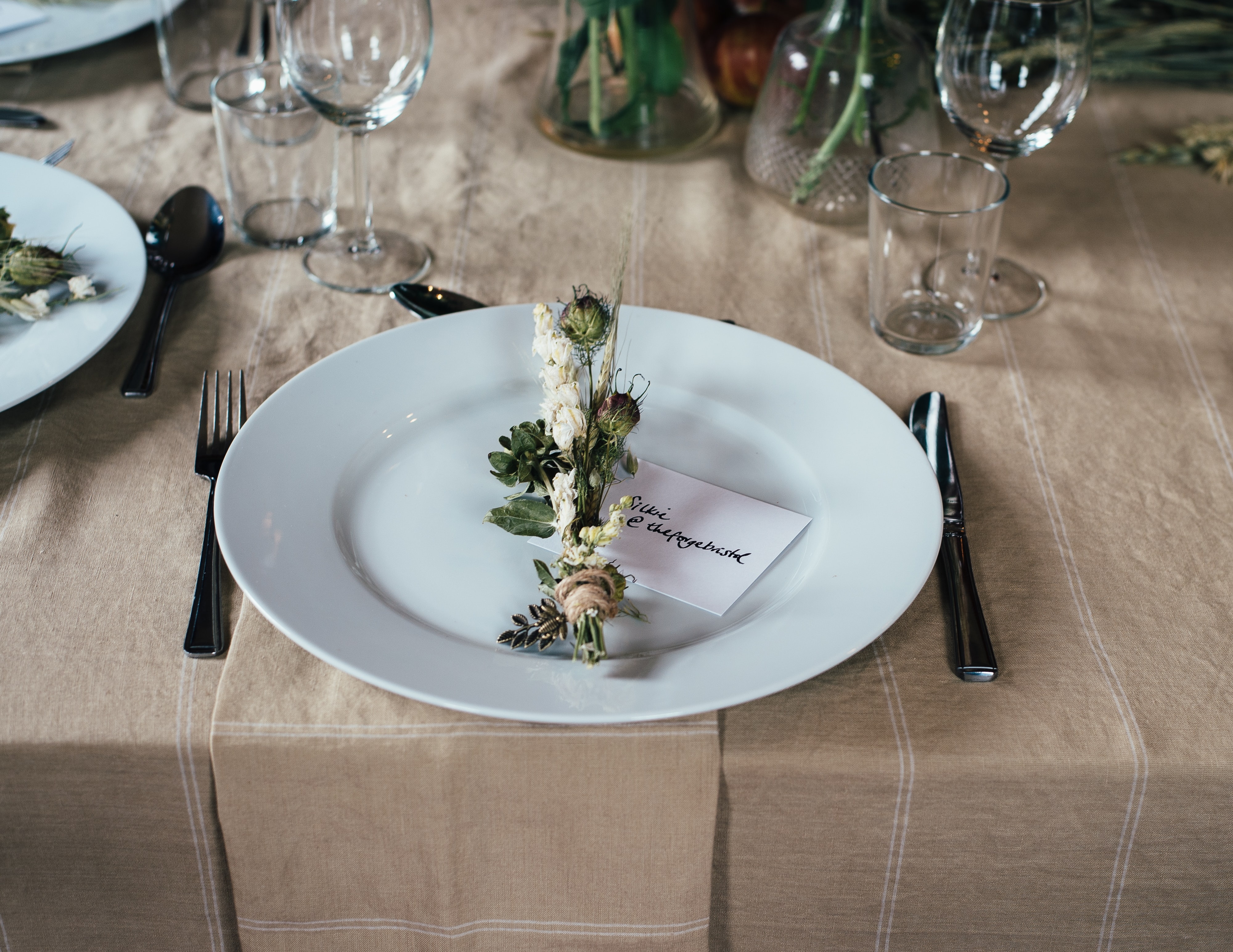 A bunch of flowers and a card on an empty white plate on a set table
