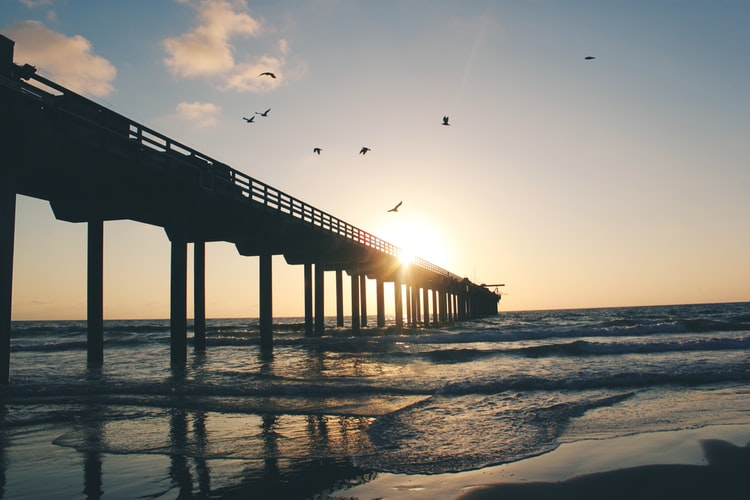 Image of the San Diego pier over the ocean at sunset.