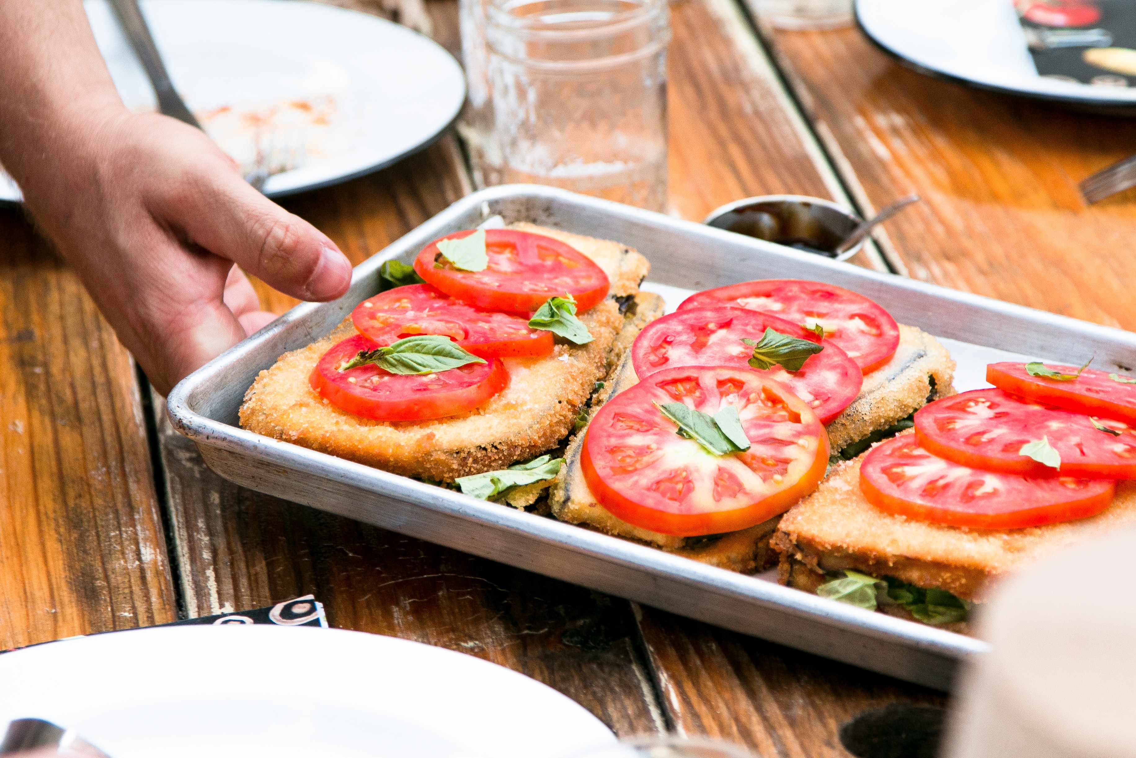 A dish topped with tomato slices and basil on a tray